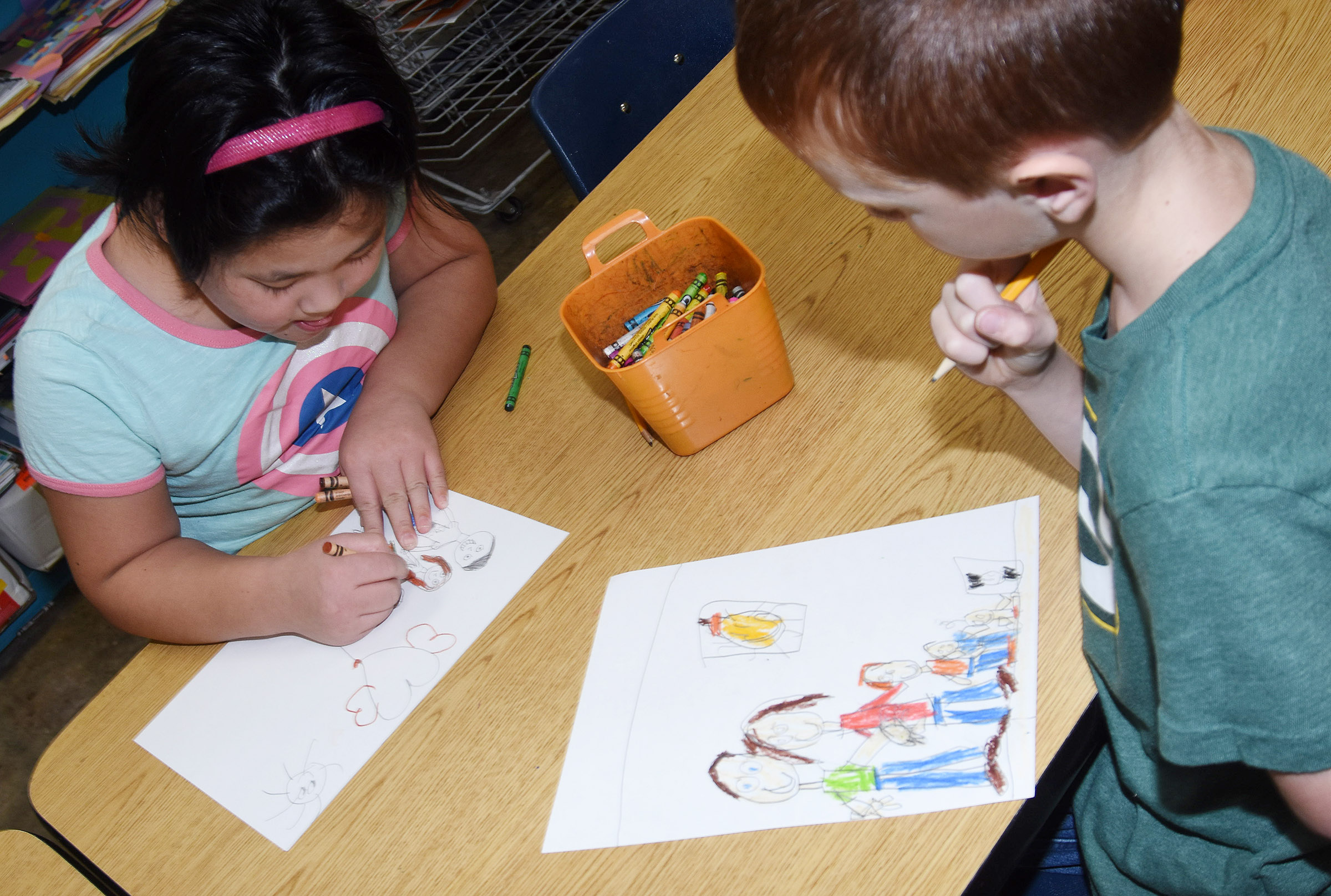 CES second-graders Vicky Li, at left, and Carson Montes work on their family portraits.