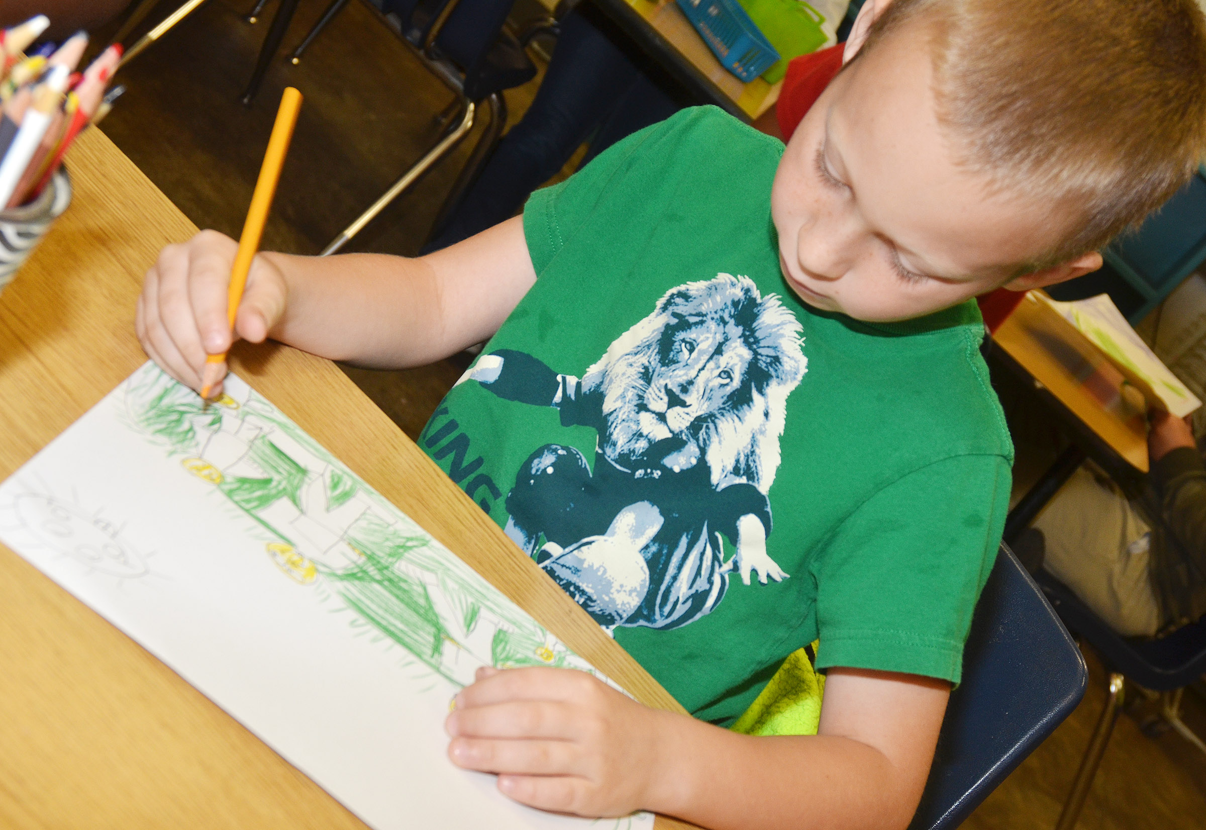 CES second-grader Raleigh Spencer colors his family portrait.