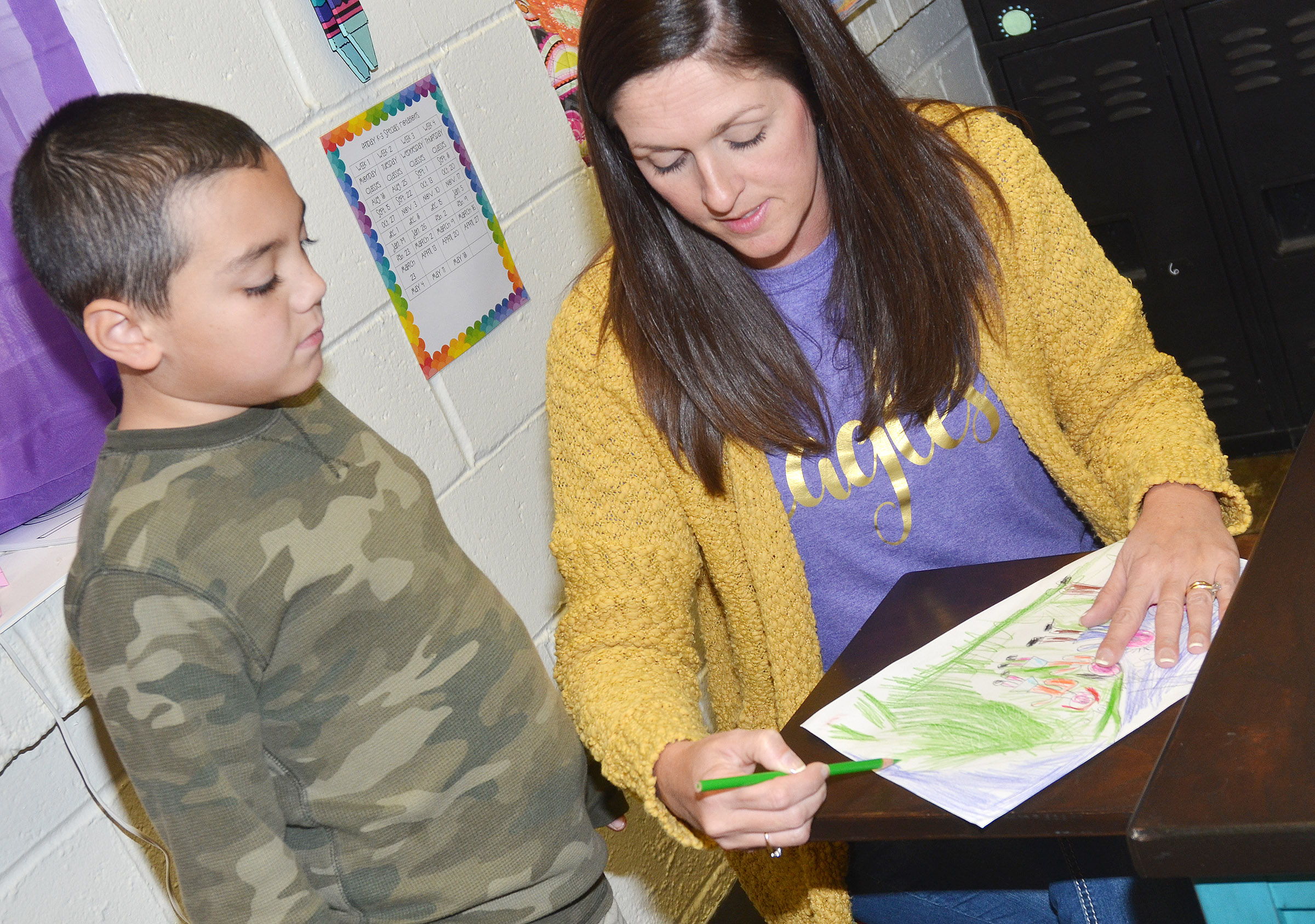 CES art teacher Adrienne Hash helps second-grader Diego Aquino as he colors his family portrait.