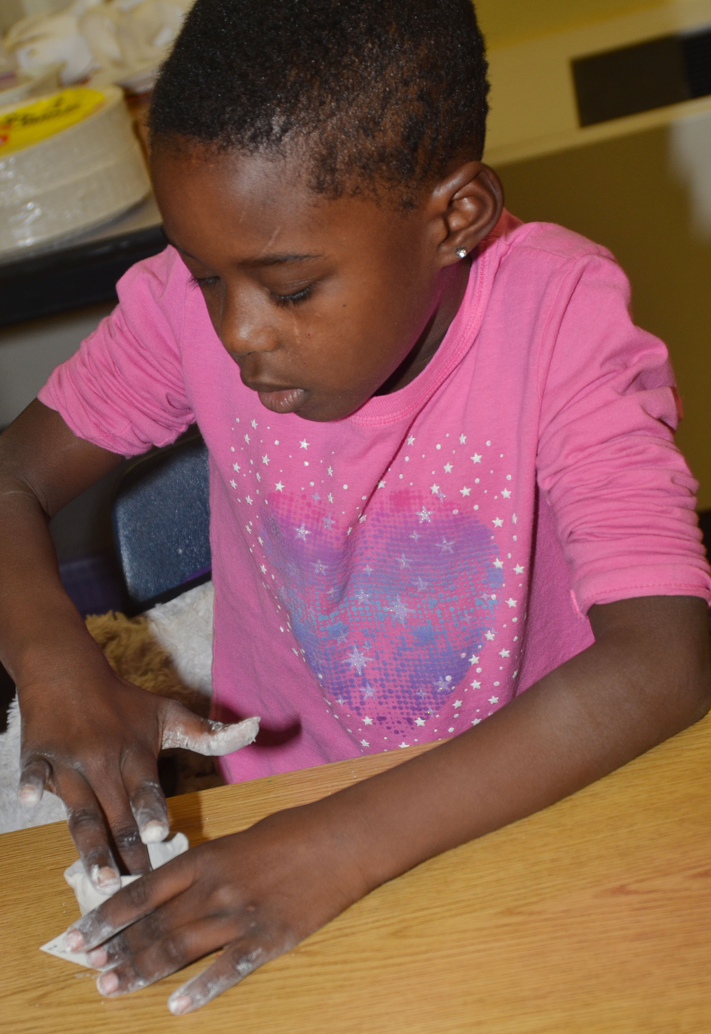 CES first-grader Zion Mitchell shapes her pot.