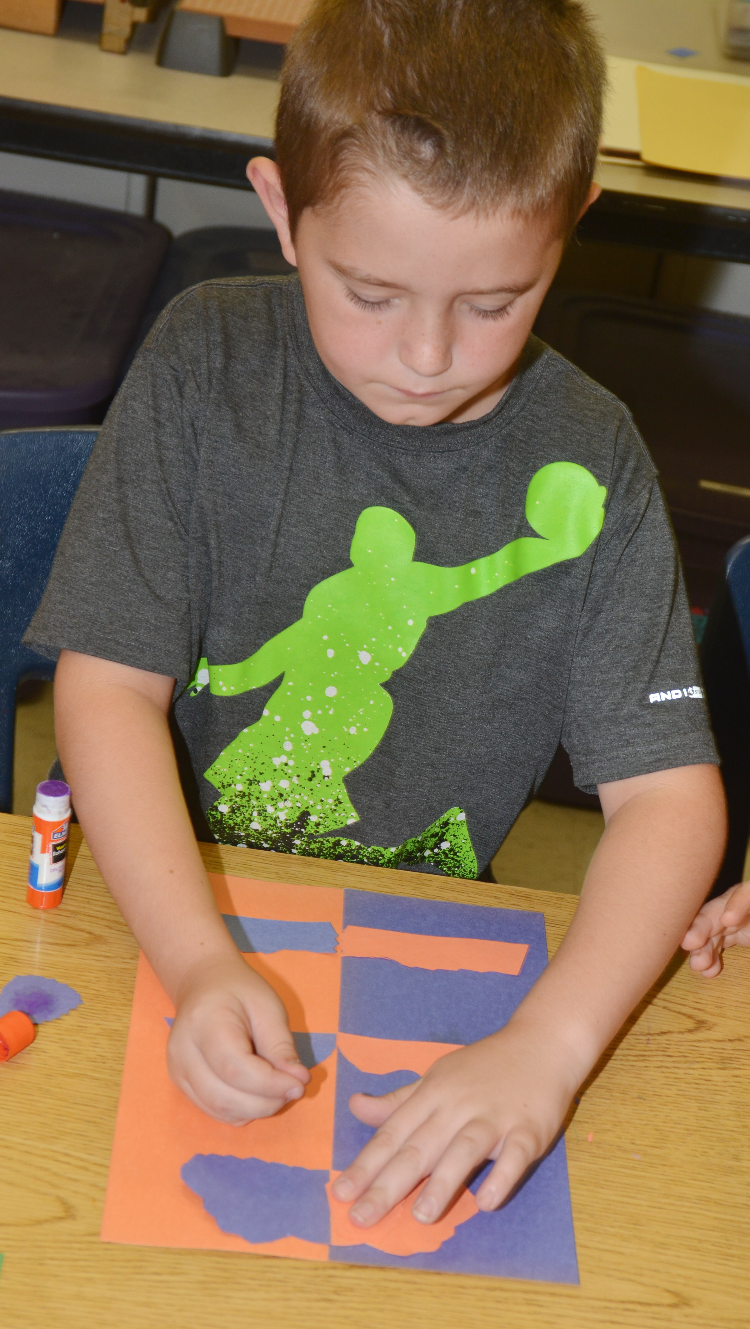 CES second-grader Kevin Bradfield glues his free form shapes.