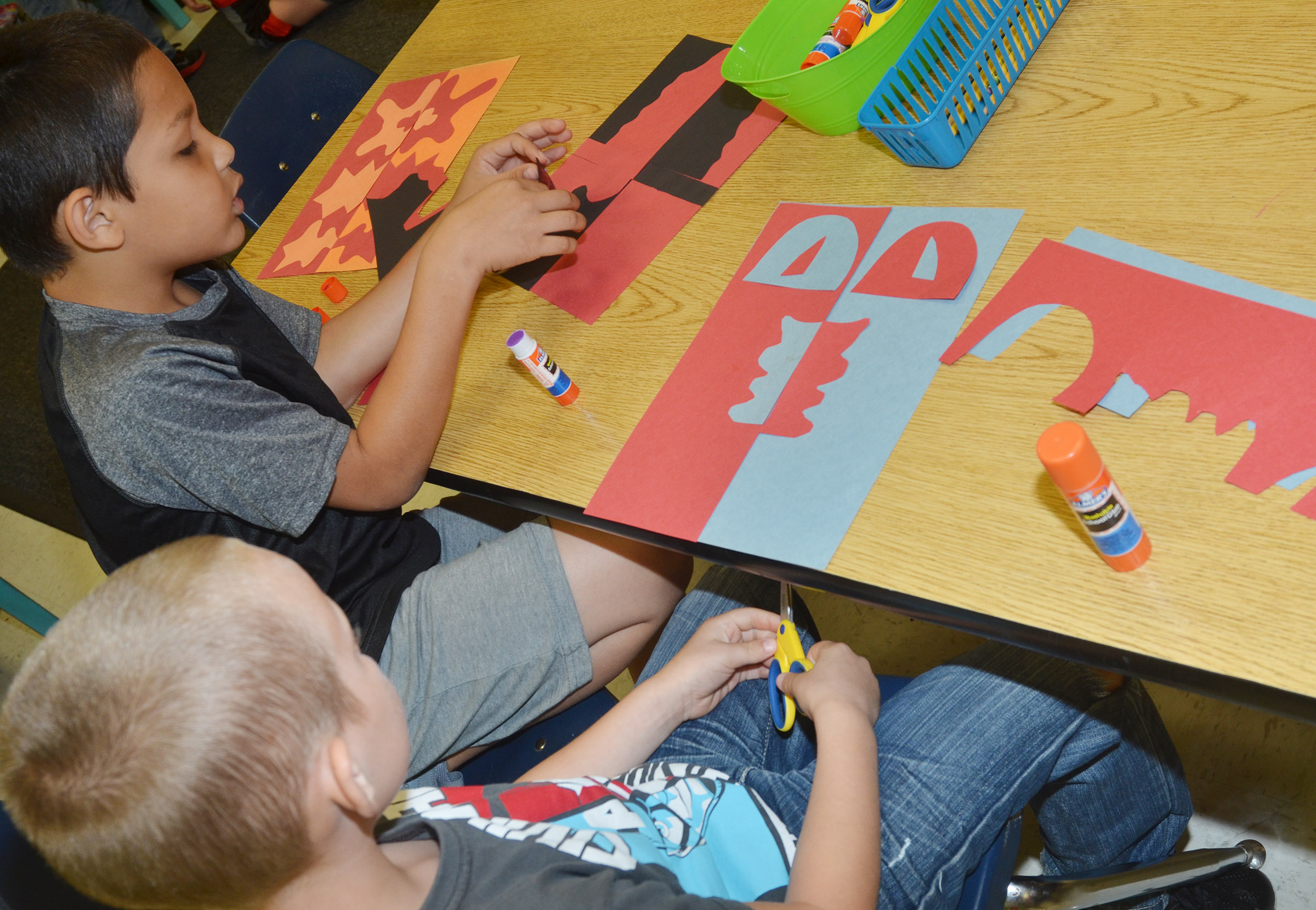 CES second-graders Makyian Bridgewater, at left, and Raleigh Spencer cut out their free form shapes.