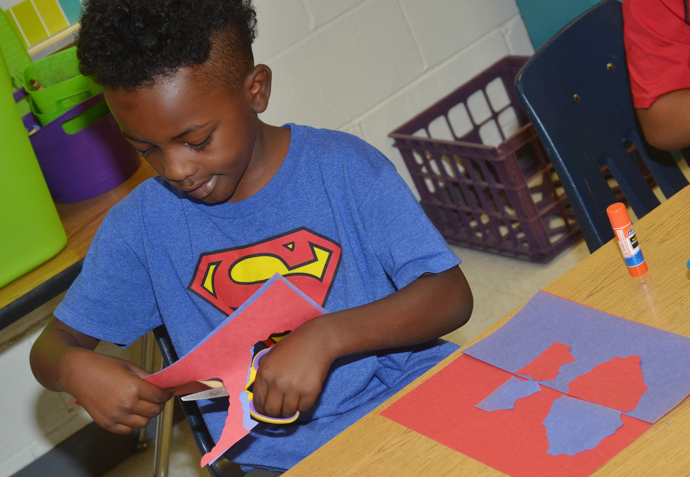 CES second-grader Drelynn Hollins cuts out his free form shapes.