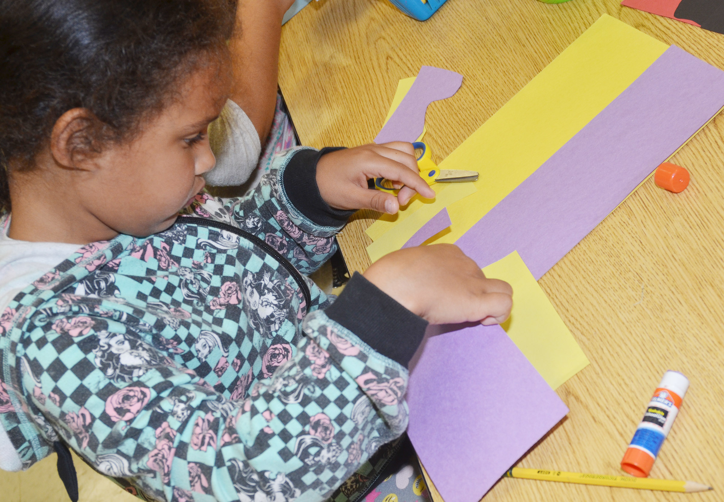 CES second-grader Amani Bridgewater cuts out her free from shapes.