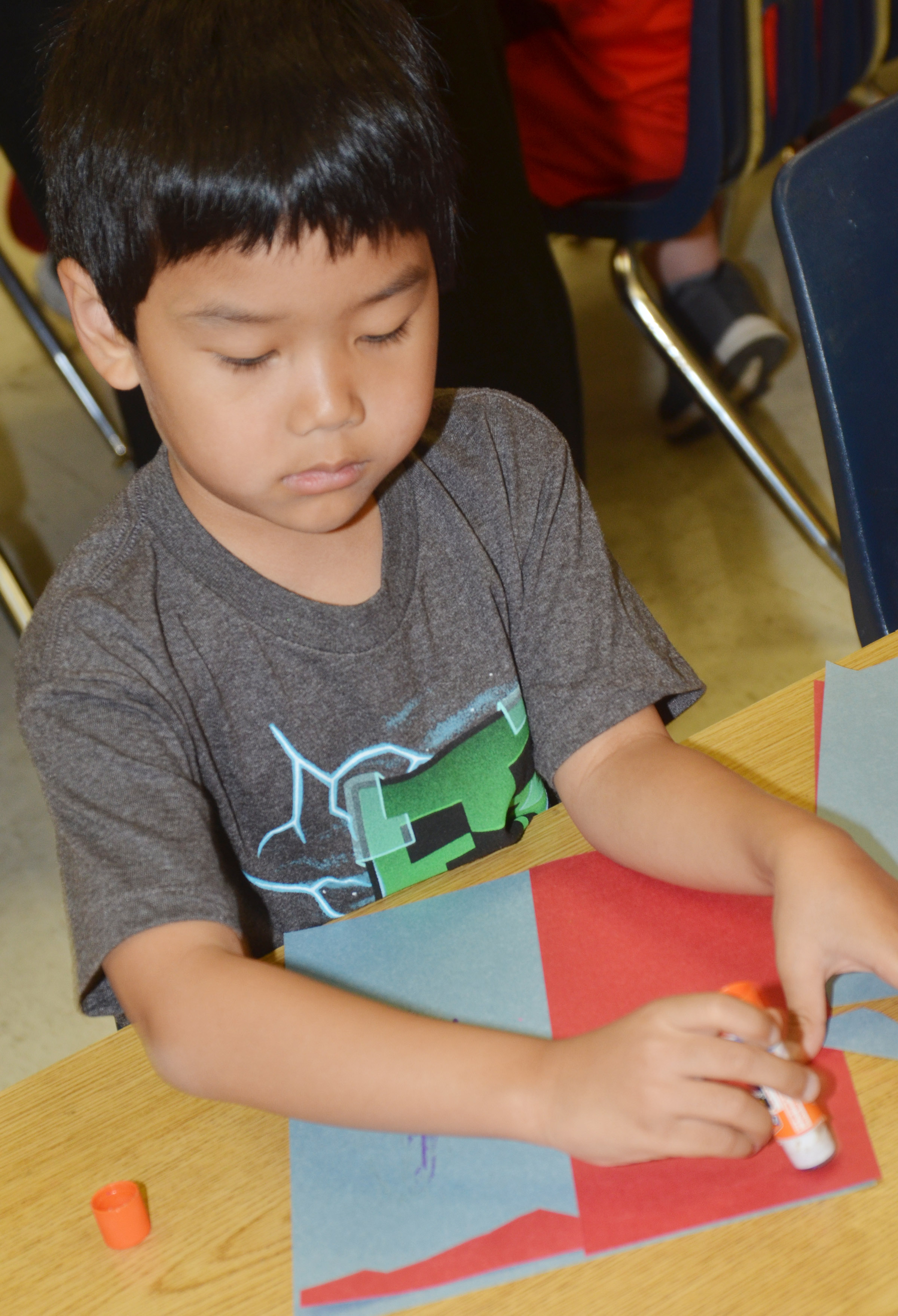 CES second-grader Zach Hak glues his free from shapes to his construction paper.