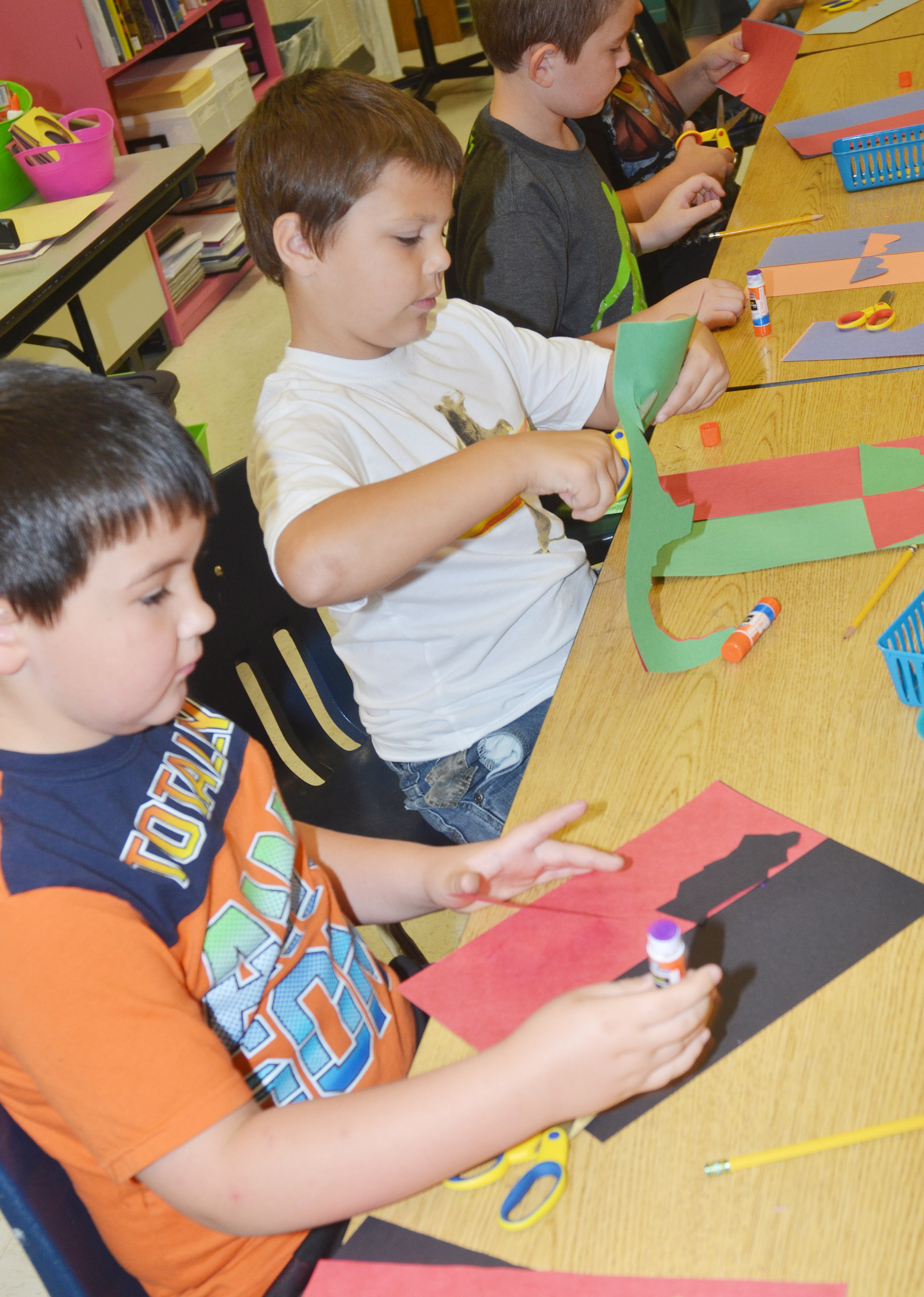 CES second-graders Braxton Giles-Osinger, at left, and Jaxson Hunt glue their free form shapes.