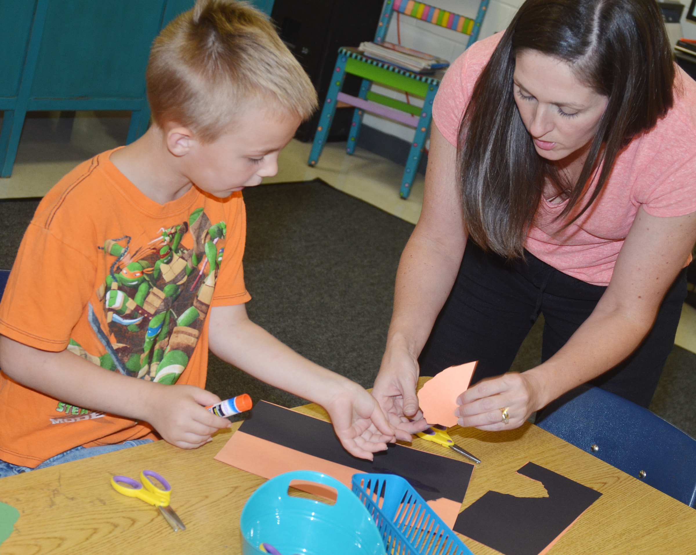 CES art teacher Adrienne Hash helps second-grader Hunter Bates glue his free form shapes.