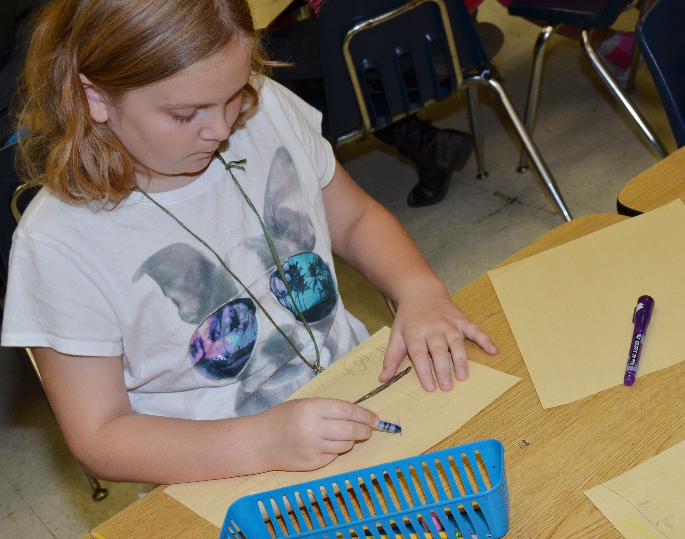 CES fourth-grader Arianna Childers colors a picture of her and her grandparents.
