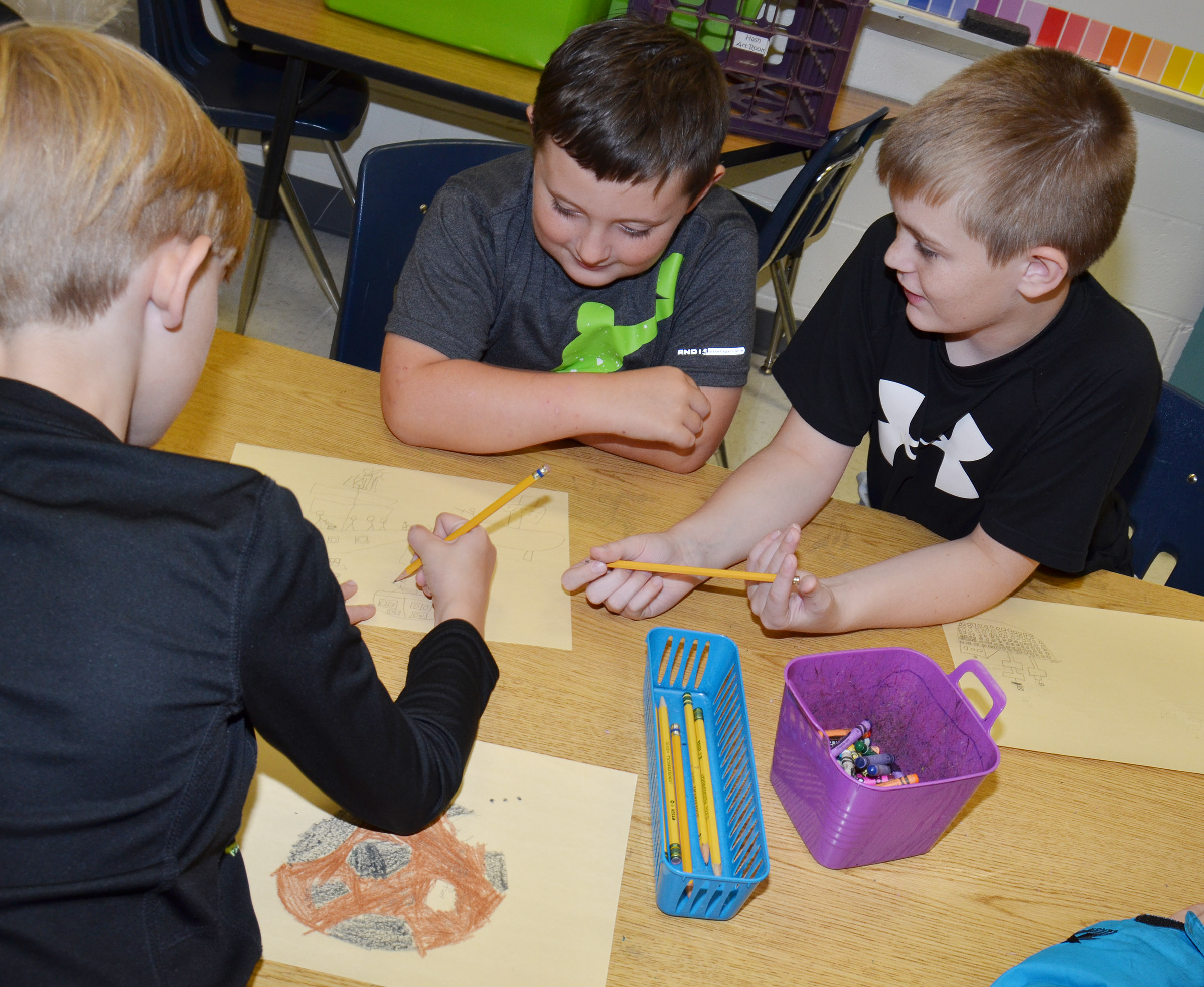 CES fourth-graders Isaiah Scharbrough, at left, and Cash Cowan talk about their drawings with classmate Jonathan Releford.