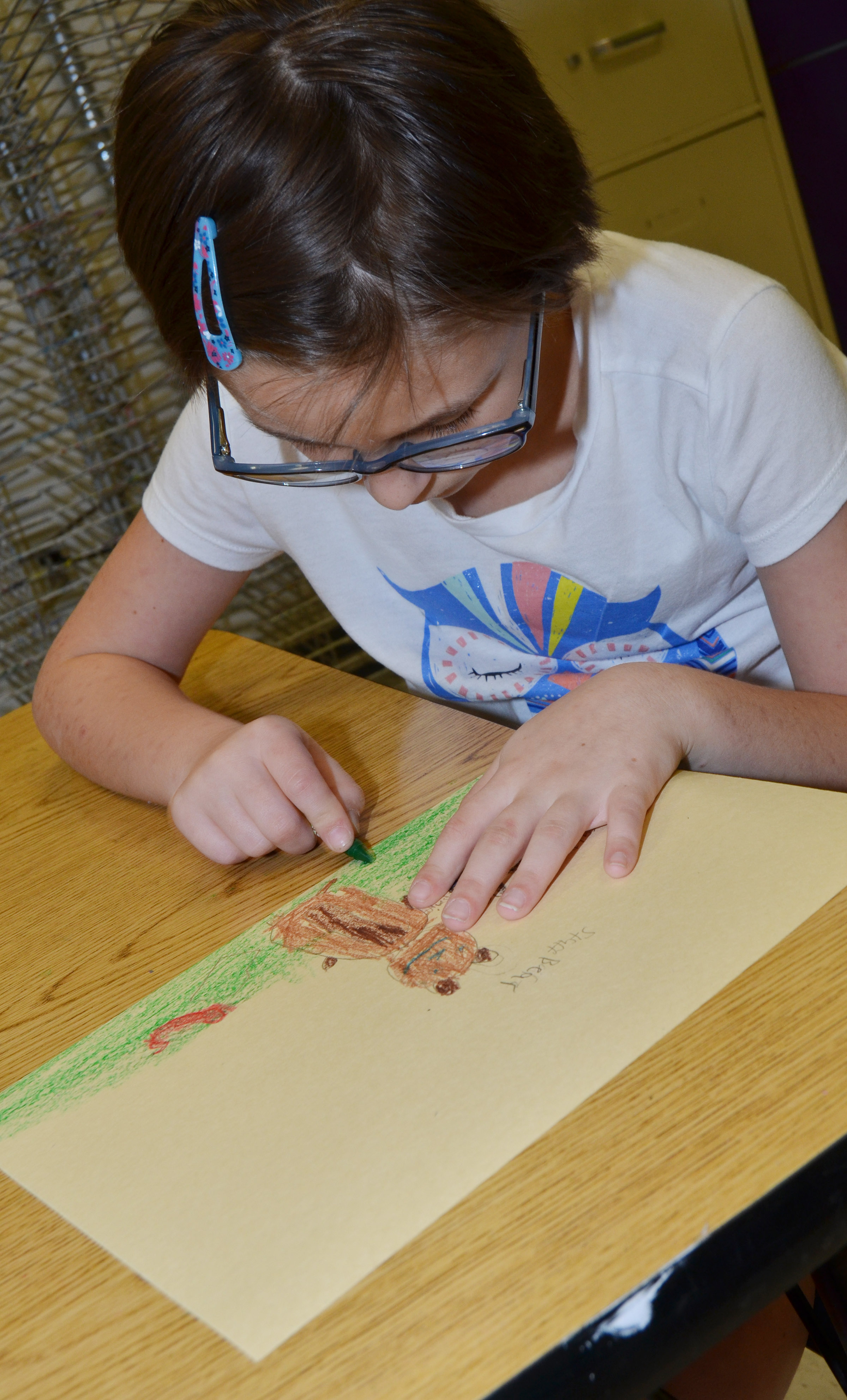 CES fourth-grader Reanna Jefferson colors her picture of her and her grandparents.