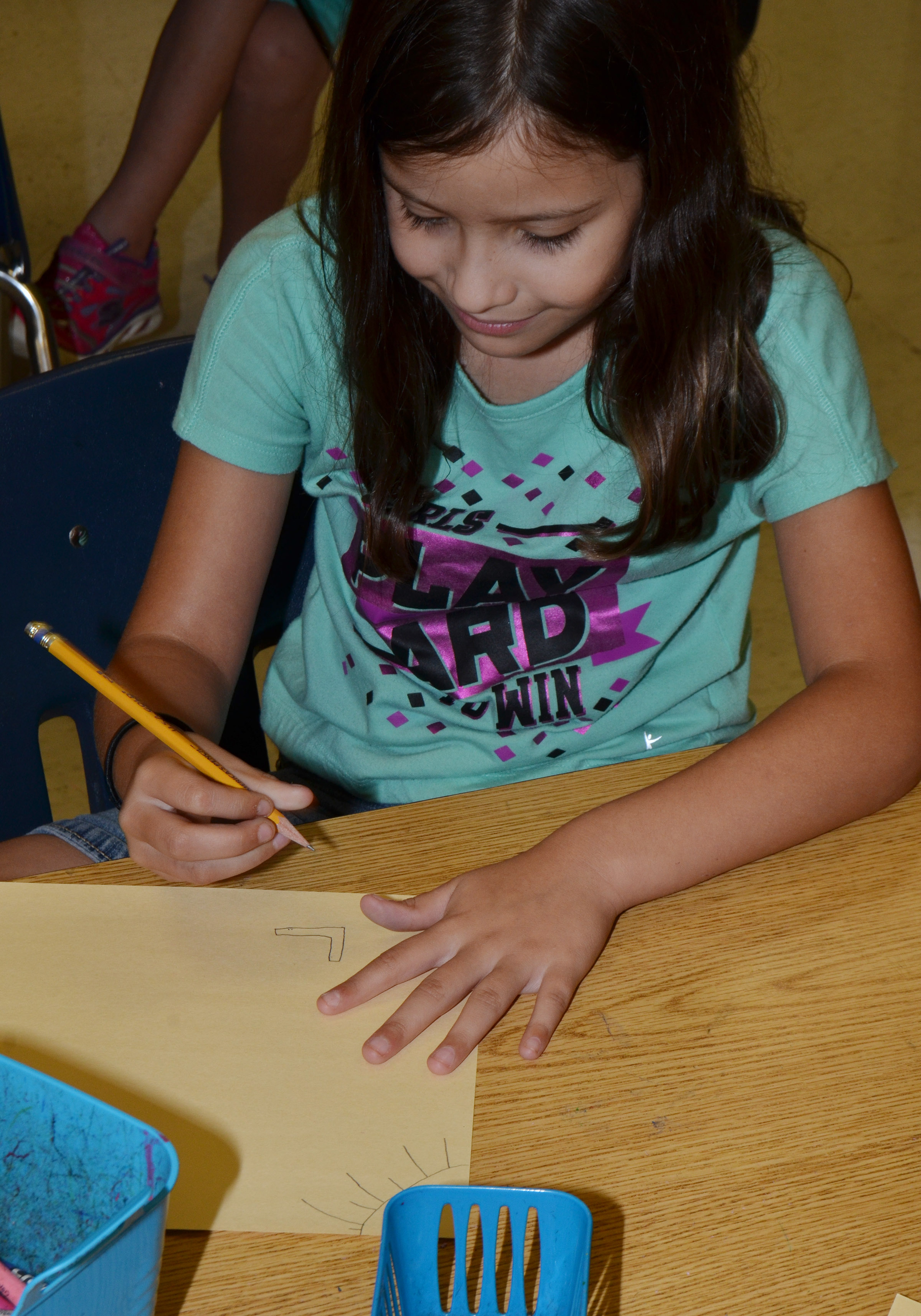CES fourth-grader Zehavan Negron draws a picture of herself with her grandparents.