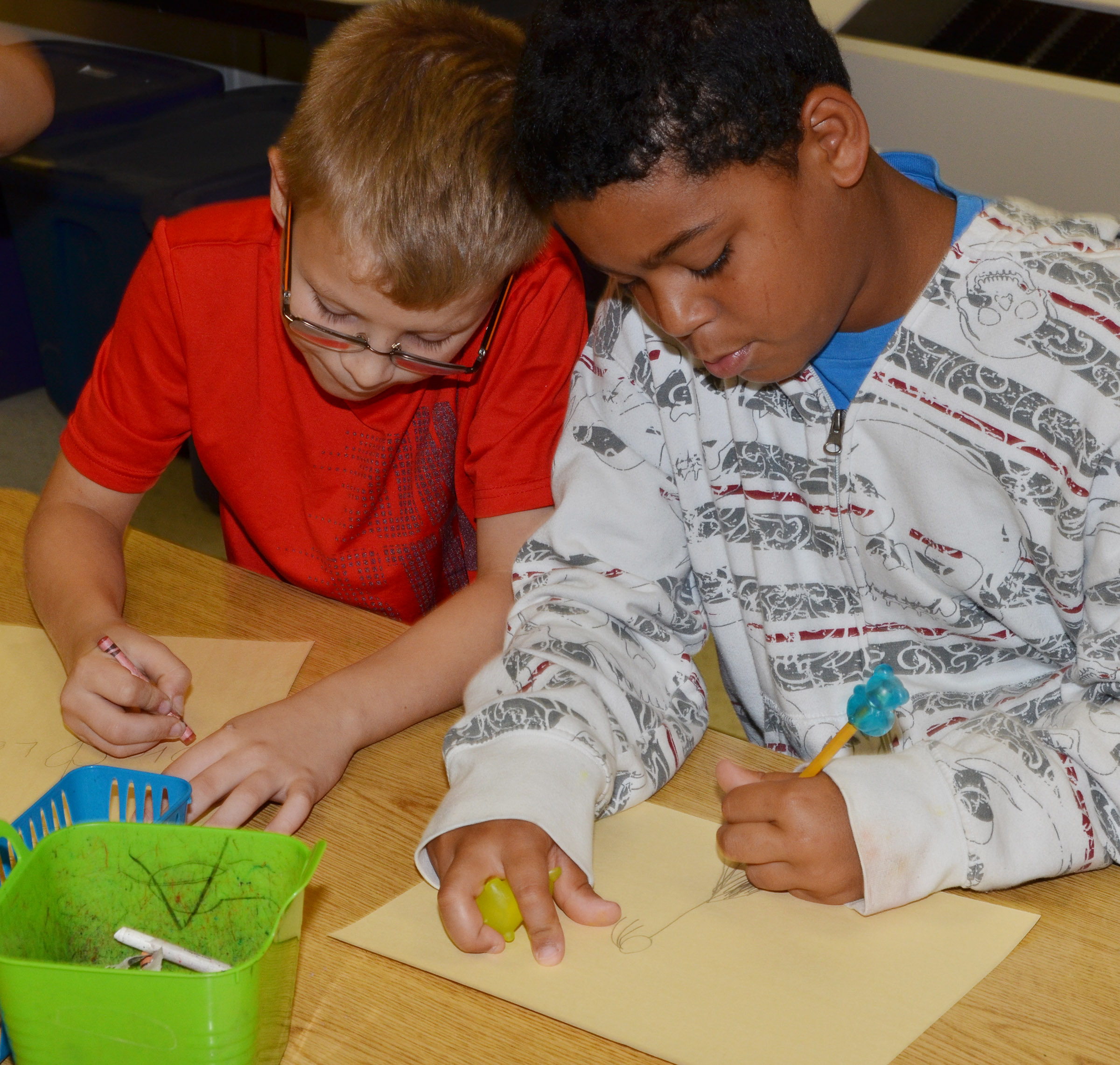 CES fourth-graders Ethan Irwin, at left, and Bryson Groves draw pictures of themselves with their grandparents.
