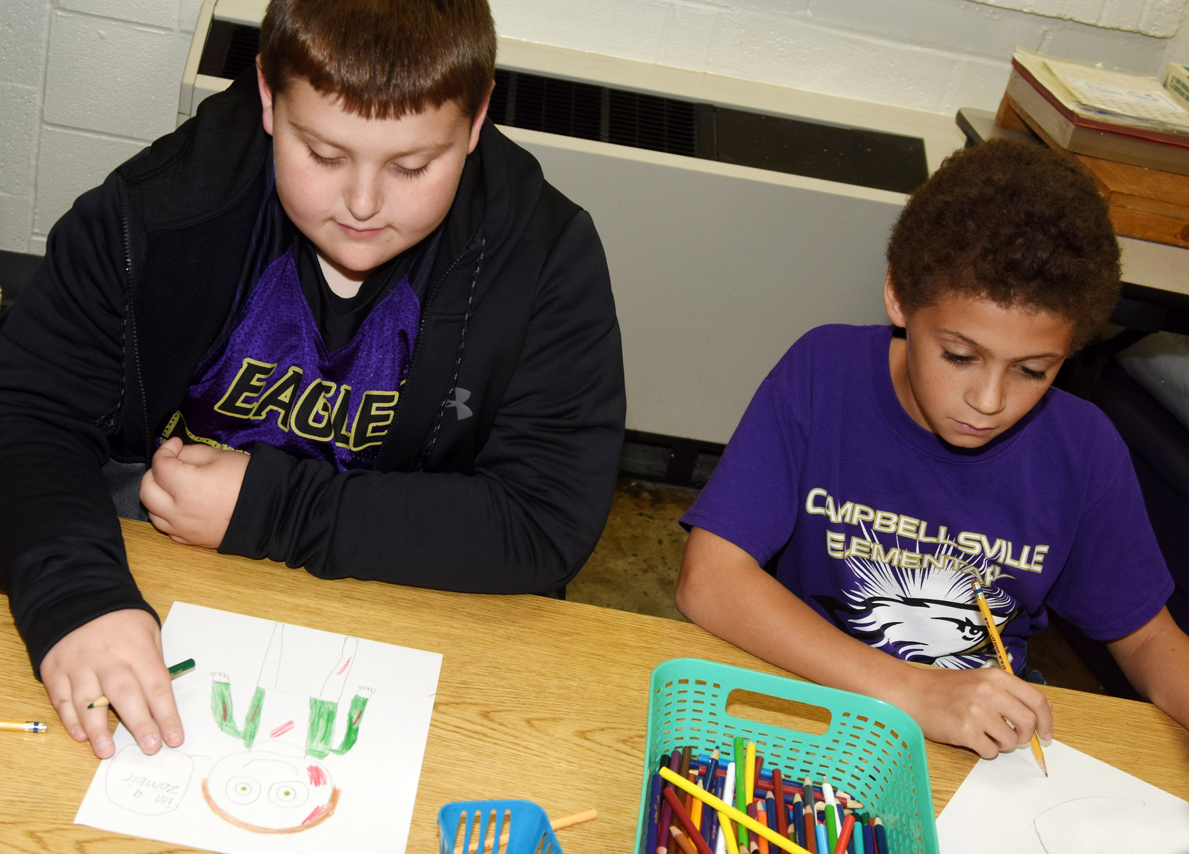 CES fourth-graders Braxton Tucker, at left, and Trever Lasley draw themselves in their Halloween costumes.