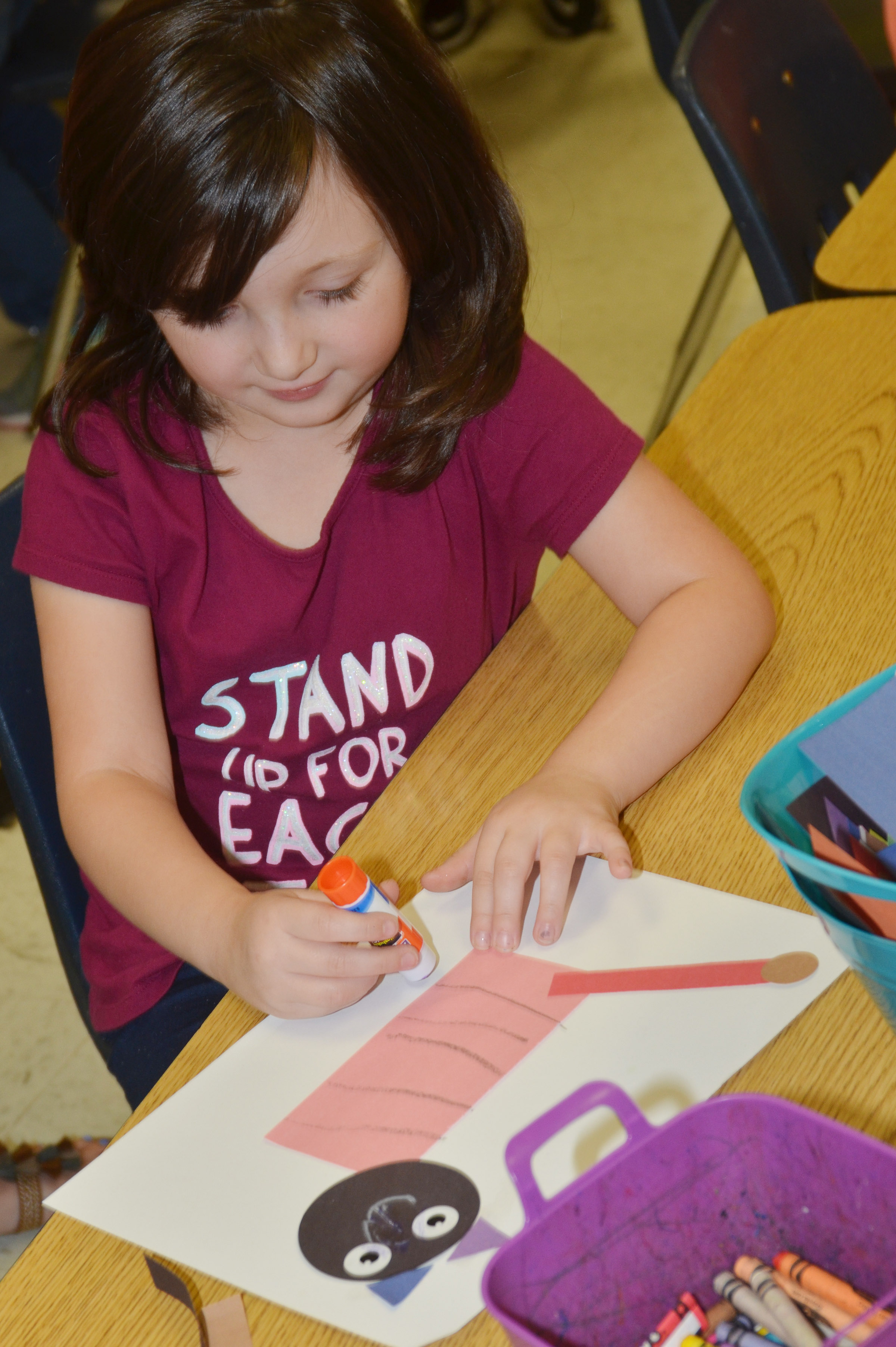 CES kindergartener Abigail Smith glues together her shape animal.