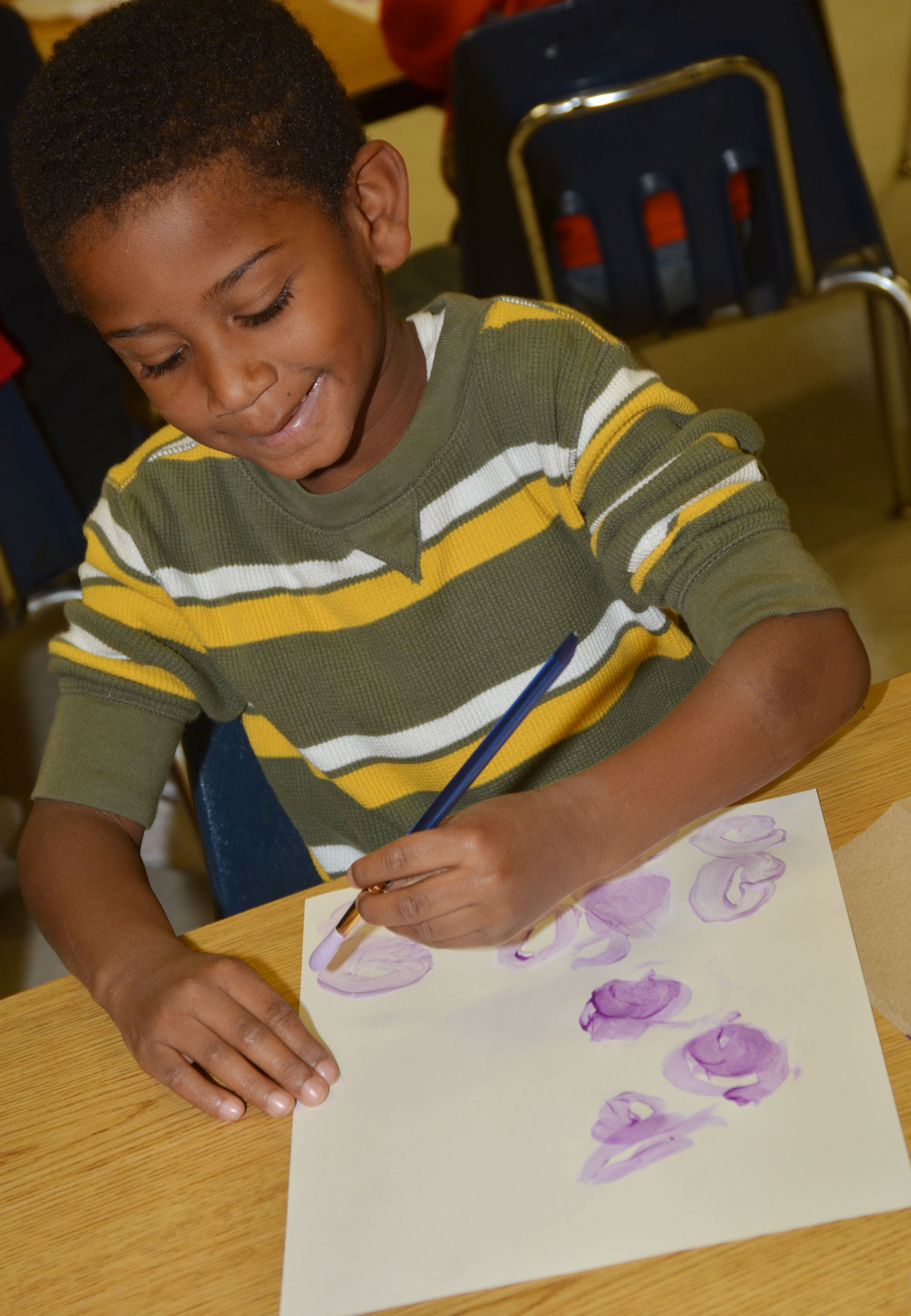 CES kindergartener Kasen Smith paints purple circles.