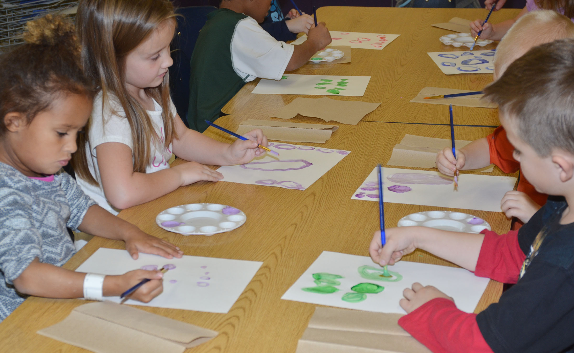 CES kindergarteners paint circles with light colors.