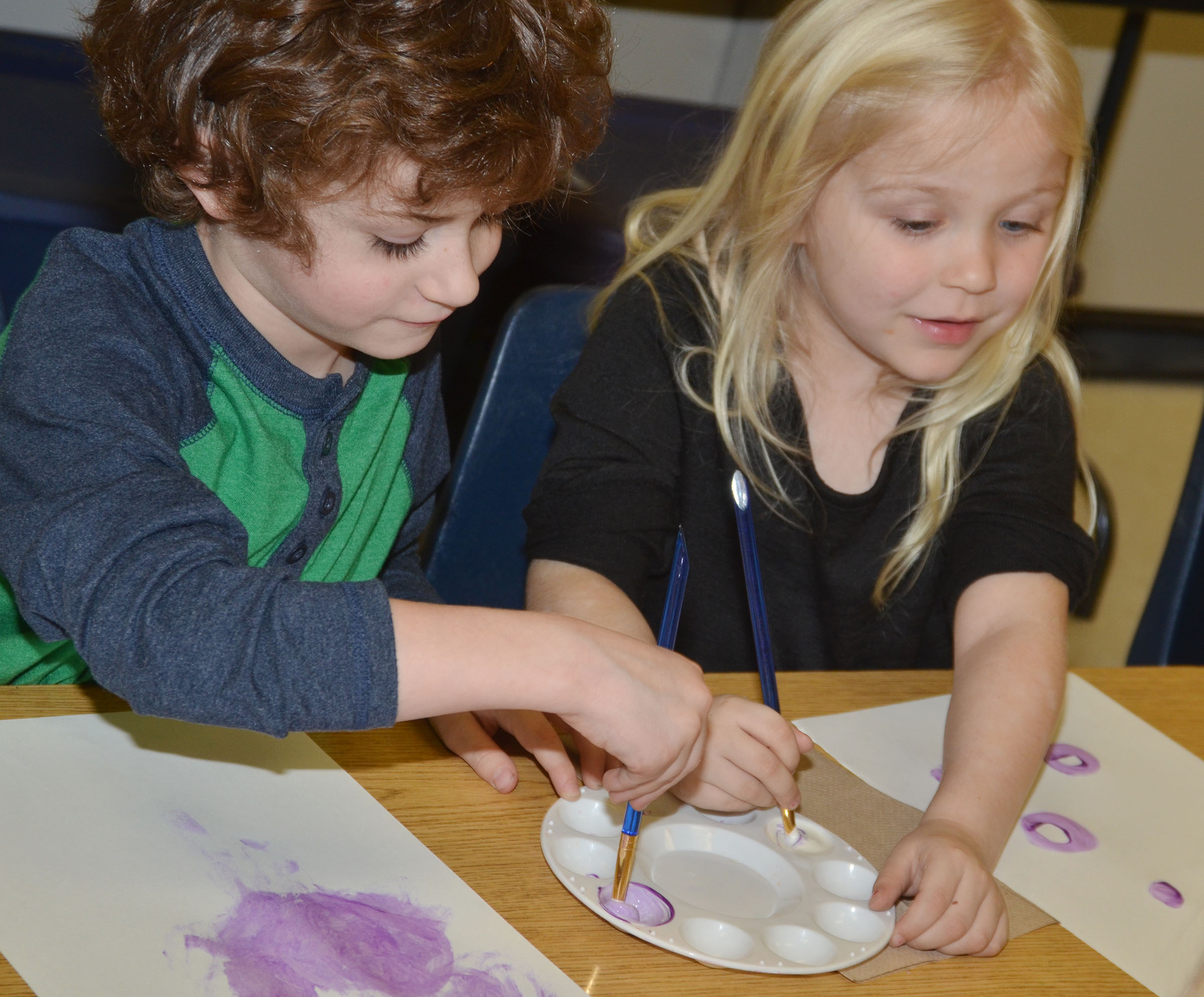 CES kindergarteners Greyson Trulock, at left, and Ava Bennett-Marr mix a light shade of purple paint.