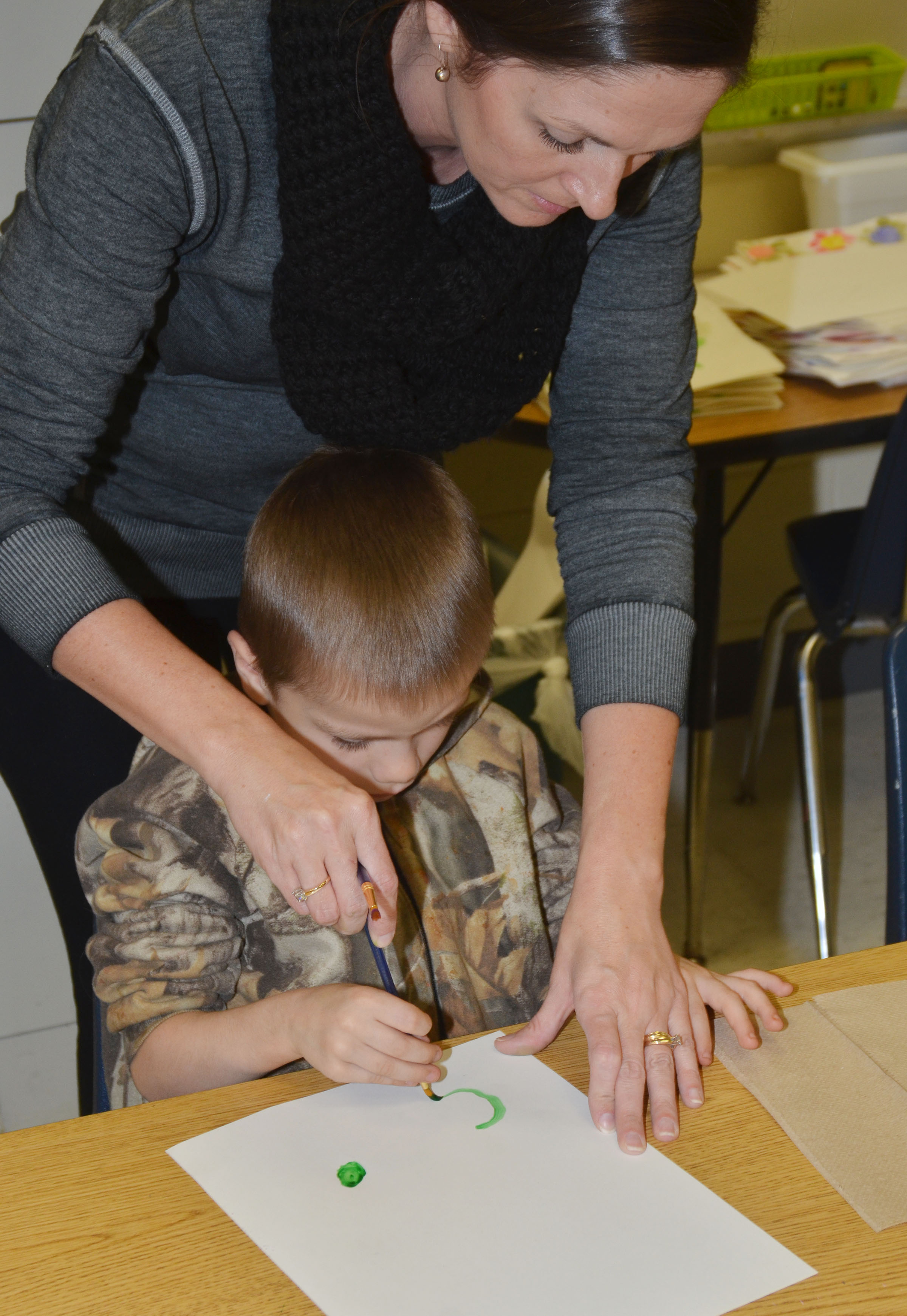 CES art teacher Adrienne Hash helps kindergartener Alex Eggers paint.