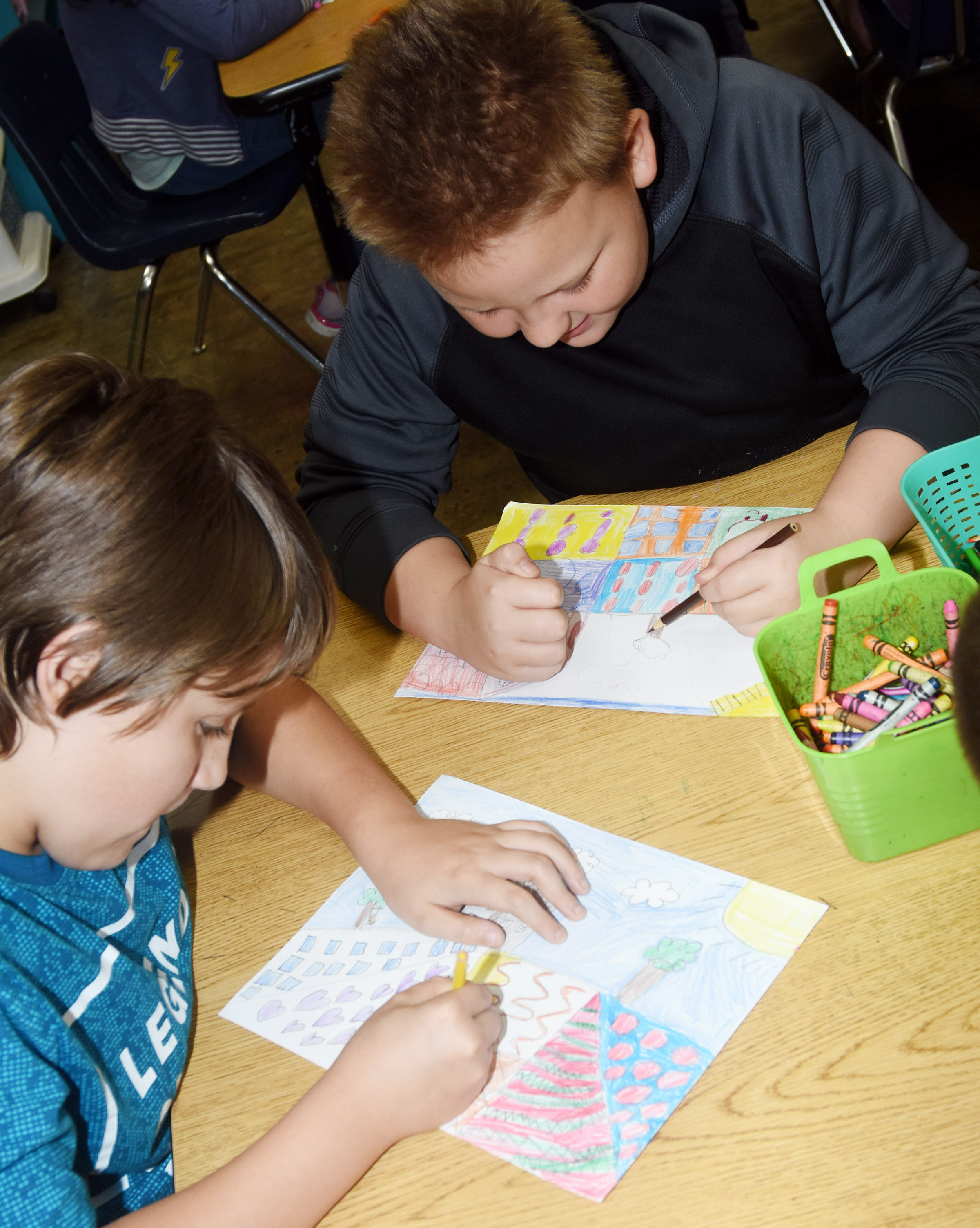 CES fourth-graders Dalton Shively, at left, and Peyton Mitchell color their landscapes.