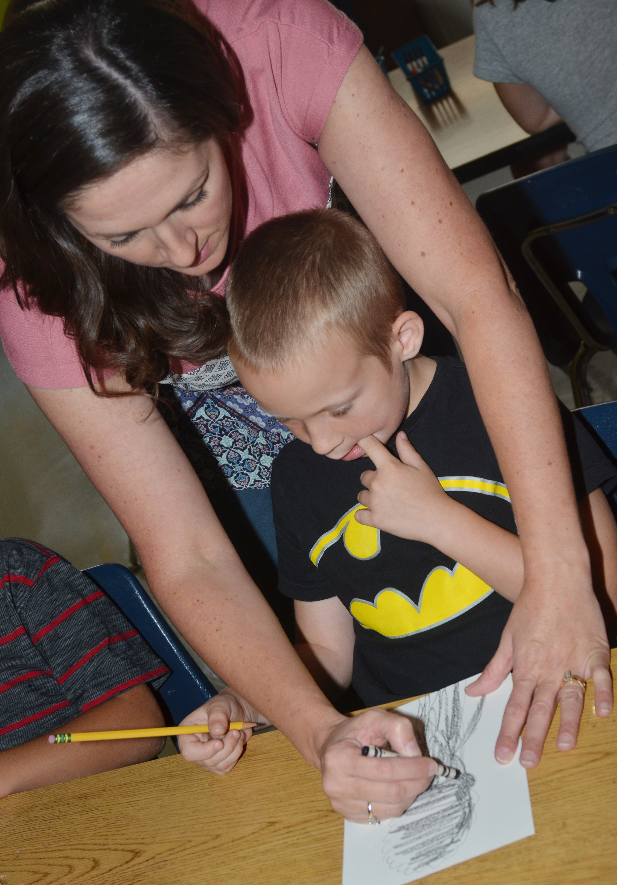CES art teacher Adrienne Hash helps second-grader Raleigh Spencer draw his line tree.