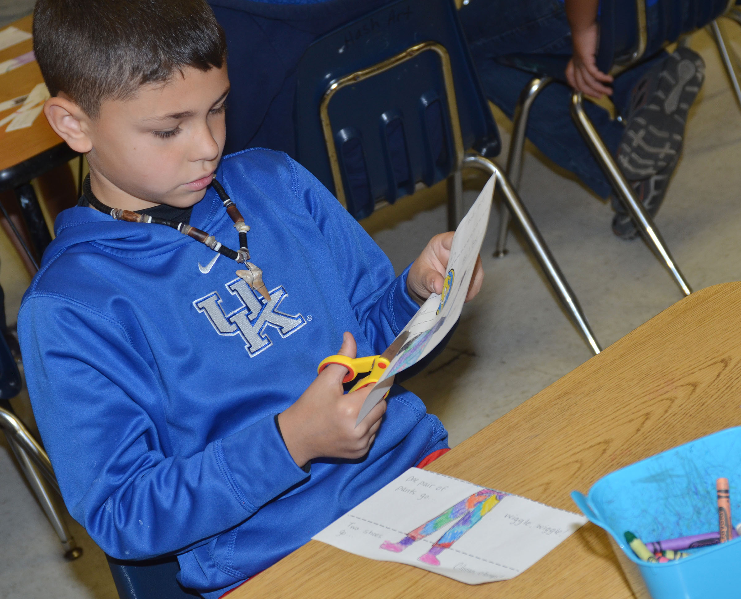CES second-grader Braygon Noegel cuts out his picture of the little old lady who wasn't afraid of anything to make his puzzle.