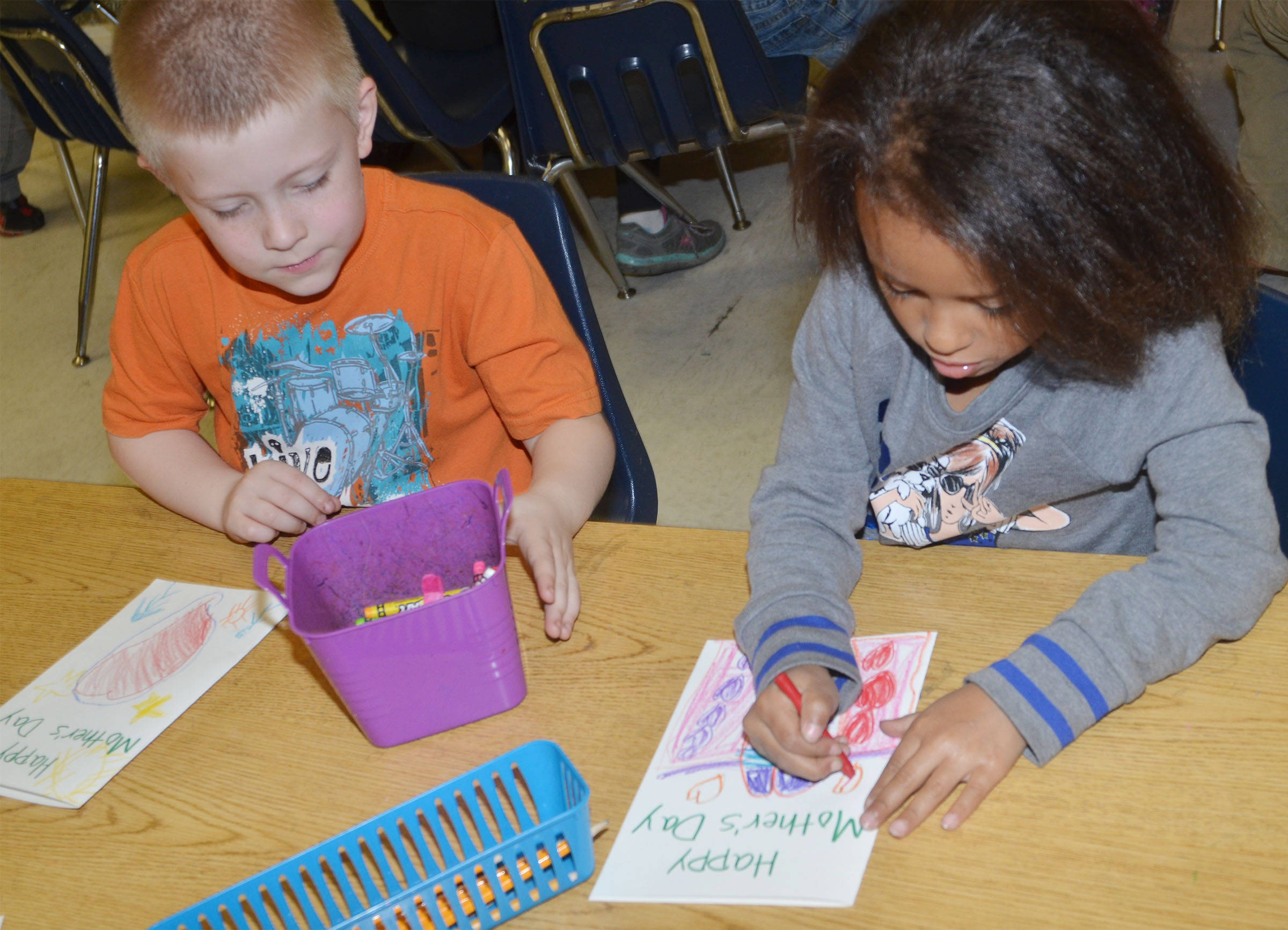 CES kindergarteners Gage Henderson, at left, and Aleja Taylor color their Mother's Day cards.