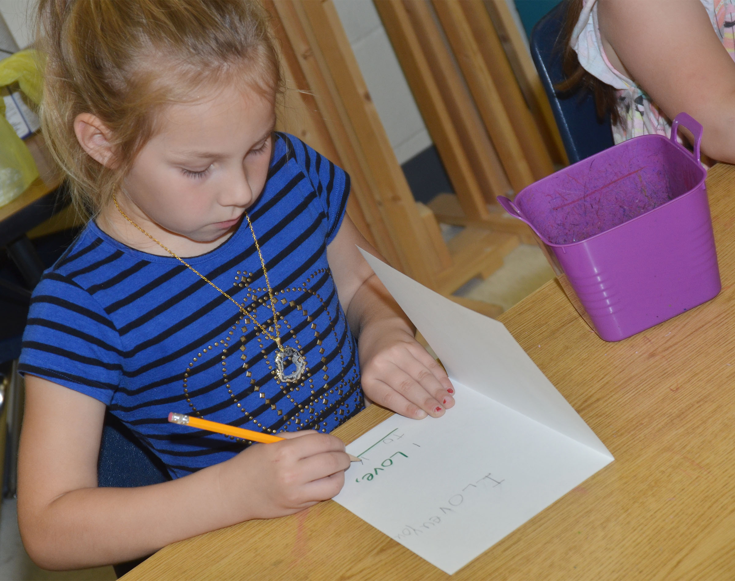 CES kindergartener Kira Dotson writes her name on her Mother's Day card.