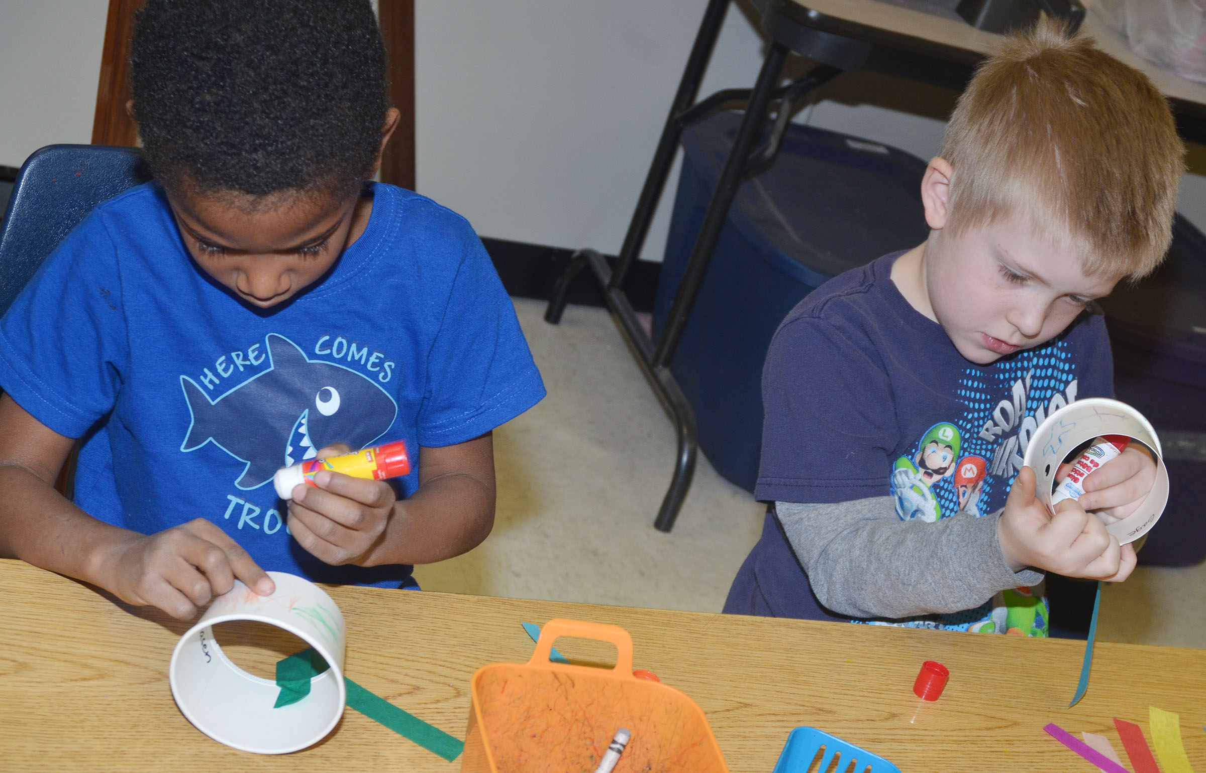 CES kindergarteners Kasen Smith, at left, and Gage Henderson glue their tentacles.