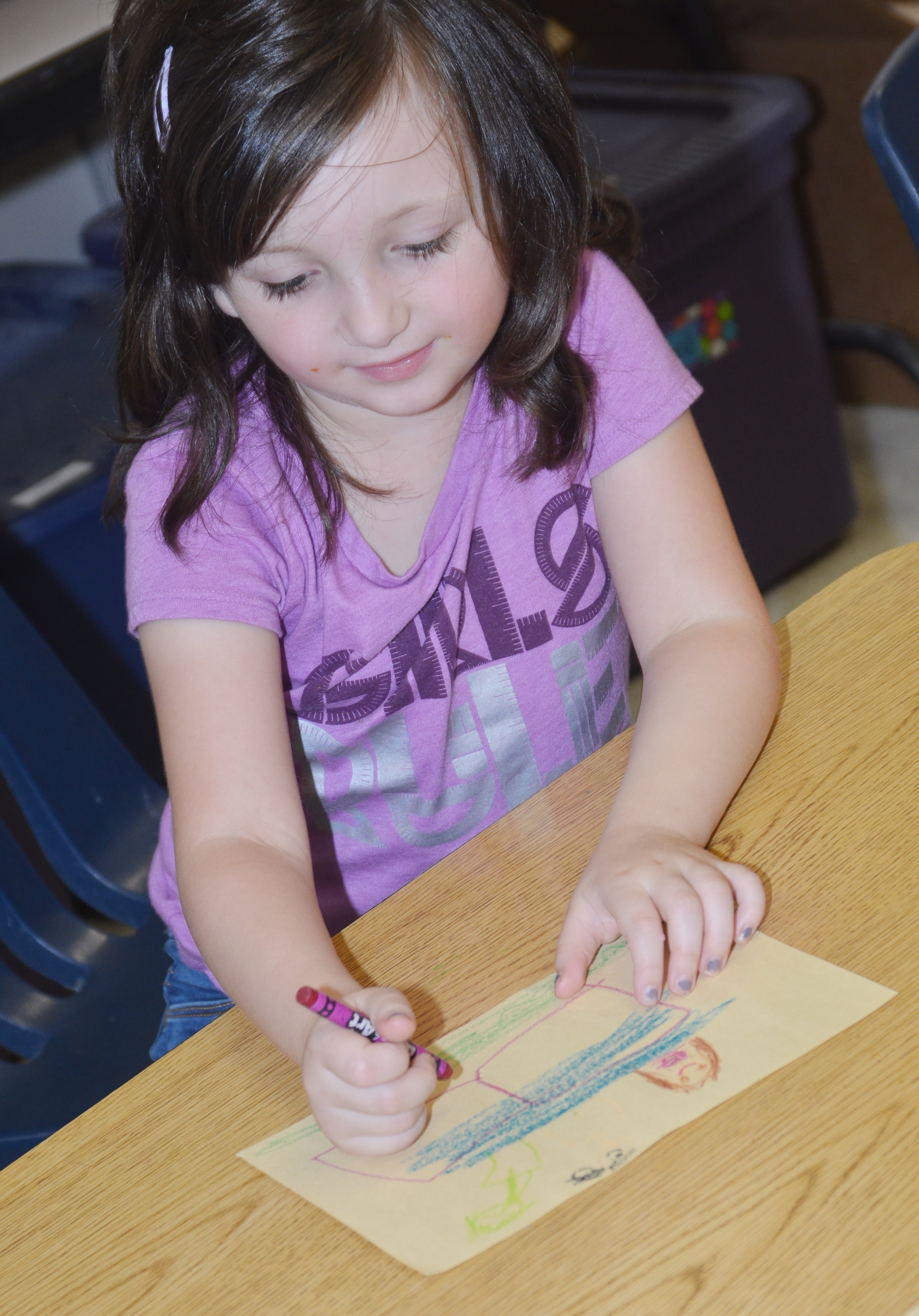 CES kindergartener Abigail Smith colors a picture of what she likes to do outside, using many types of lines.