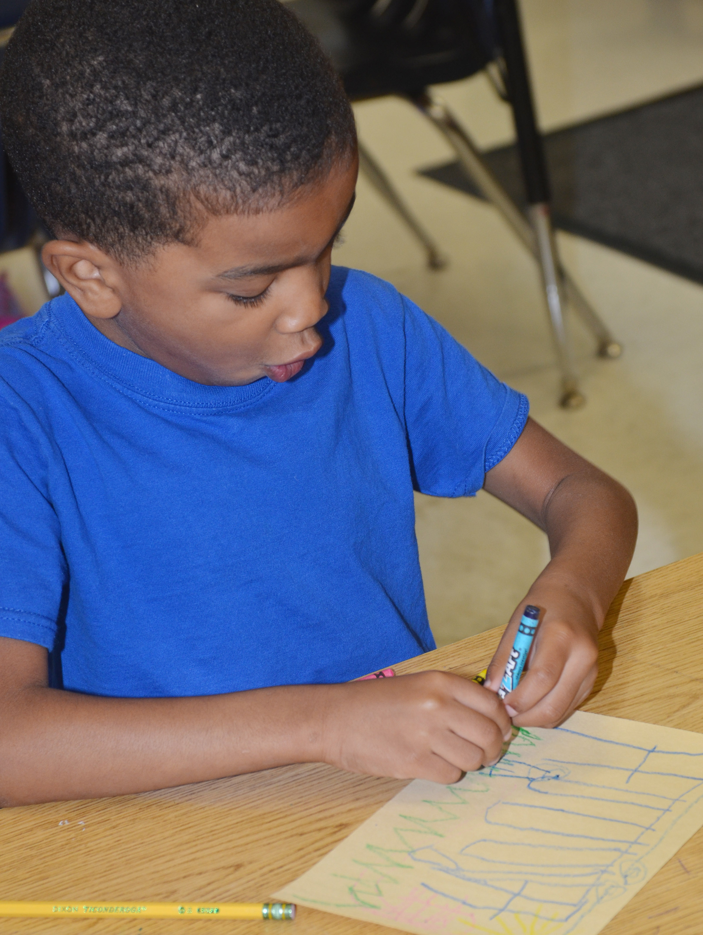 CES kindergartener Kaiyden Vancleave colors a picture of what he likes to do outside, using many types of lines.