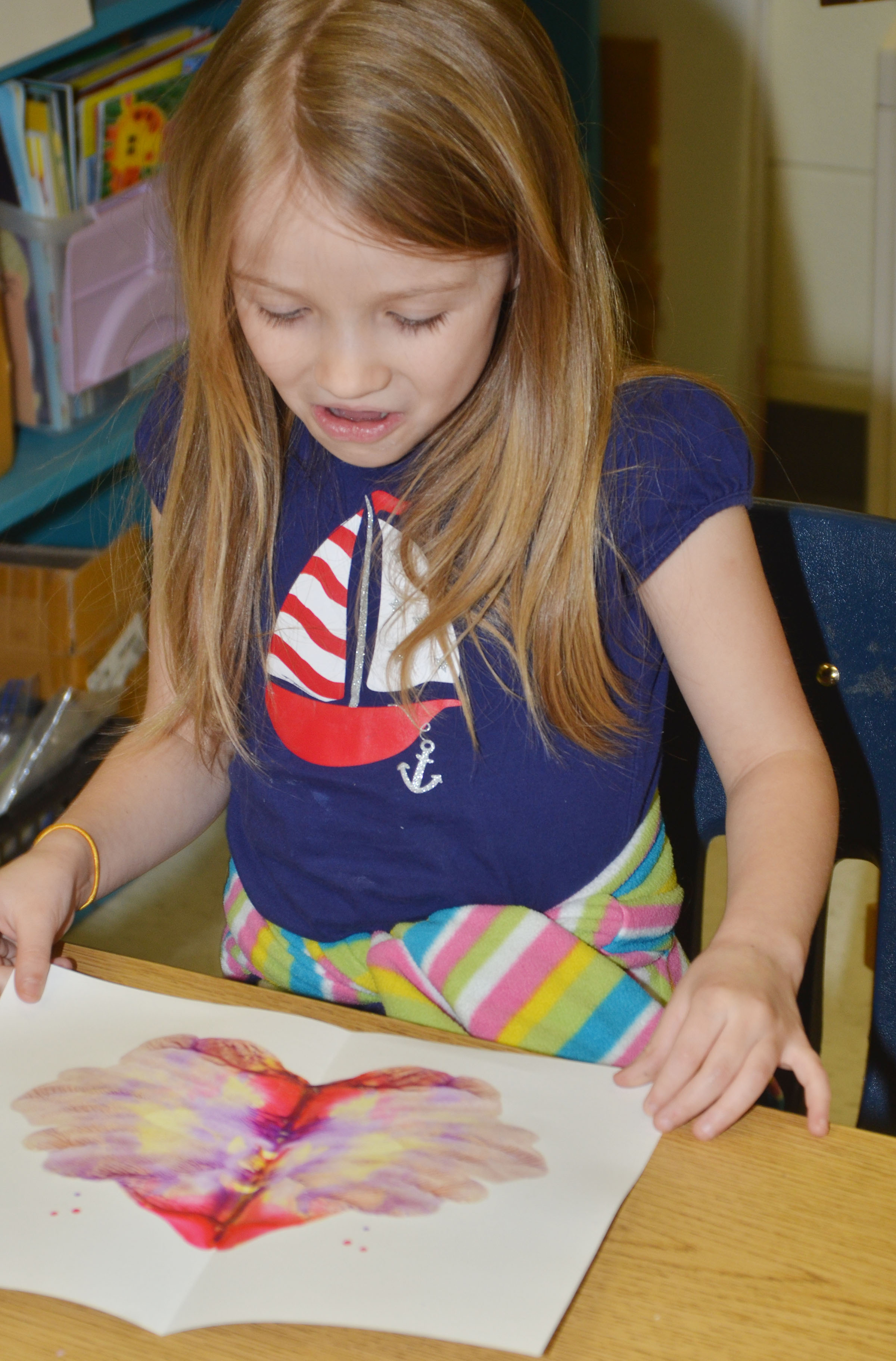 CES kindergartener Leah Covey opens her monoprint.