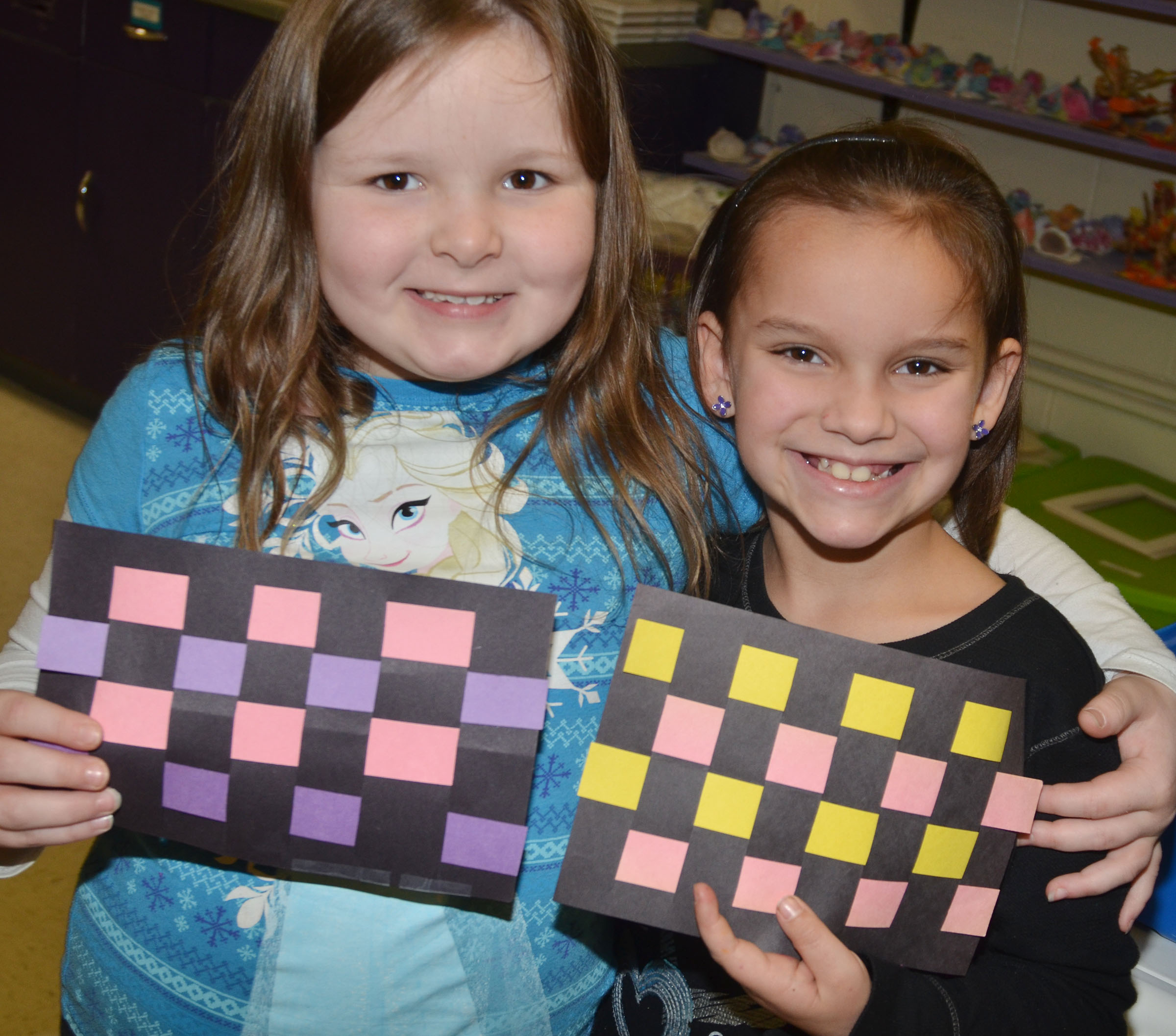 CES first-graders Kierra Maupin, at left, and Adriana Agent hold their finished mats.