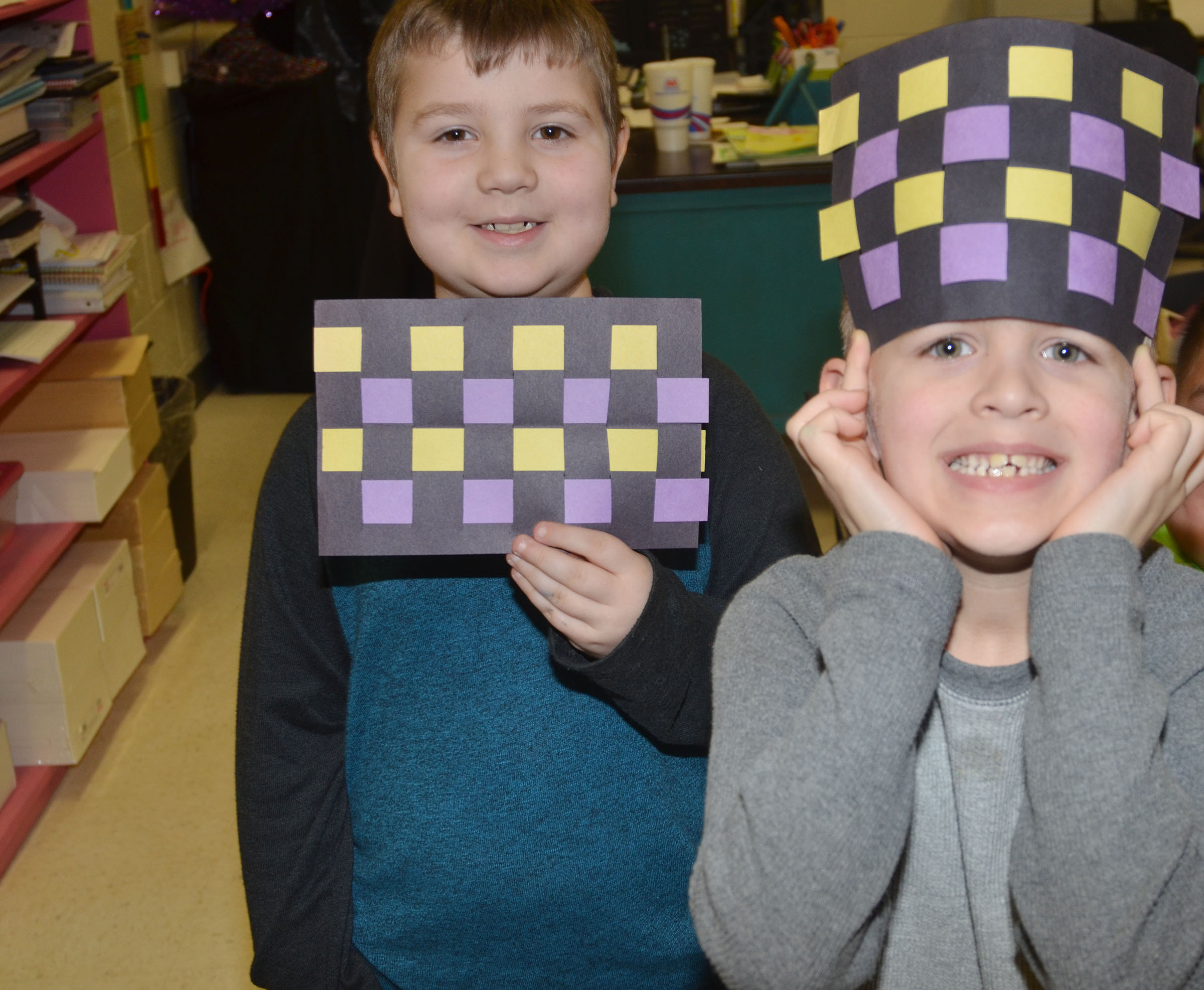 CES first-grader Luke Mardis holds his finished mat, as classmate Logan Weddle wears his.