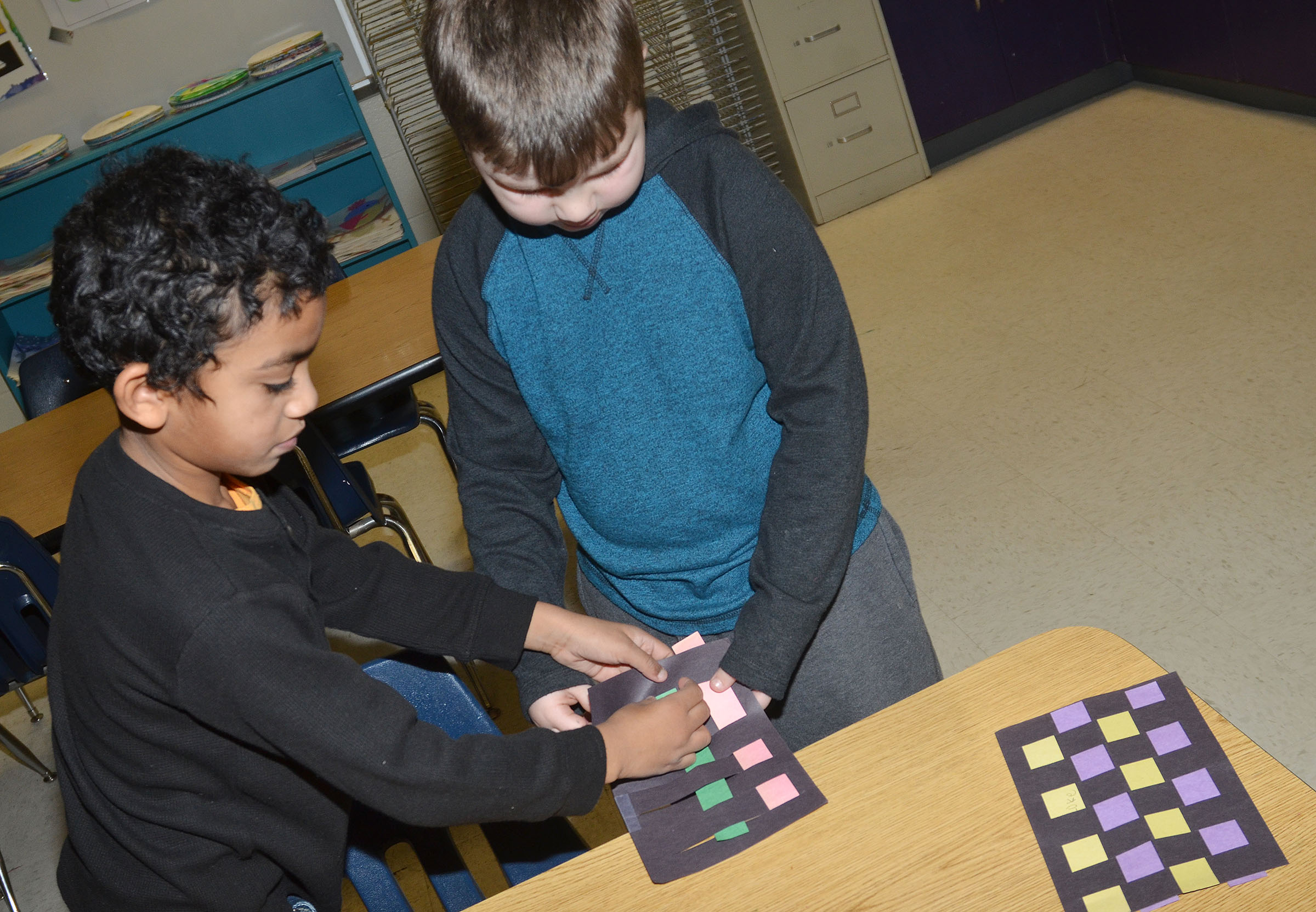 CES first-grader Luke Mardis, at right, helps classmate Enoch Smith with his mat.