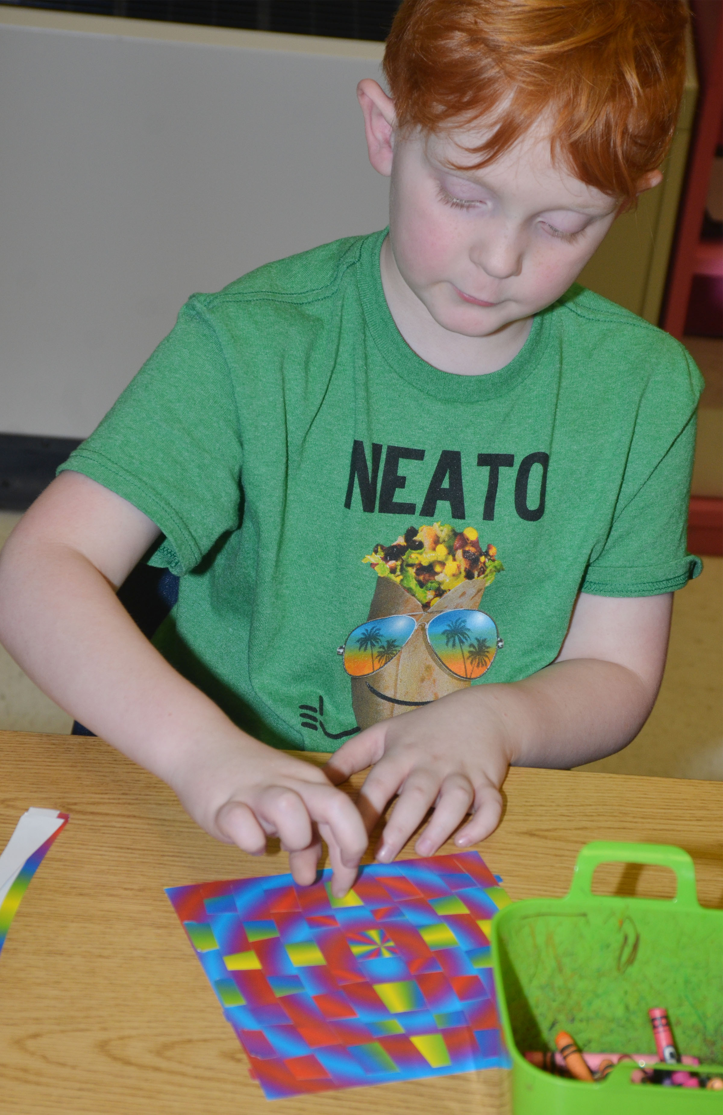CES second-grader Gavin Martin finishes his paper weaving.