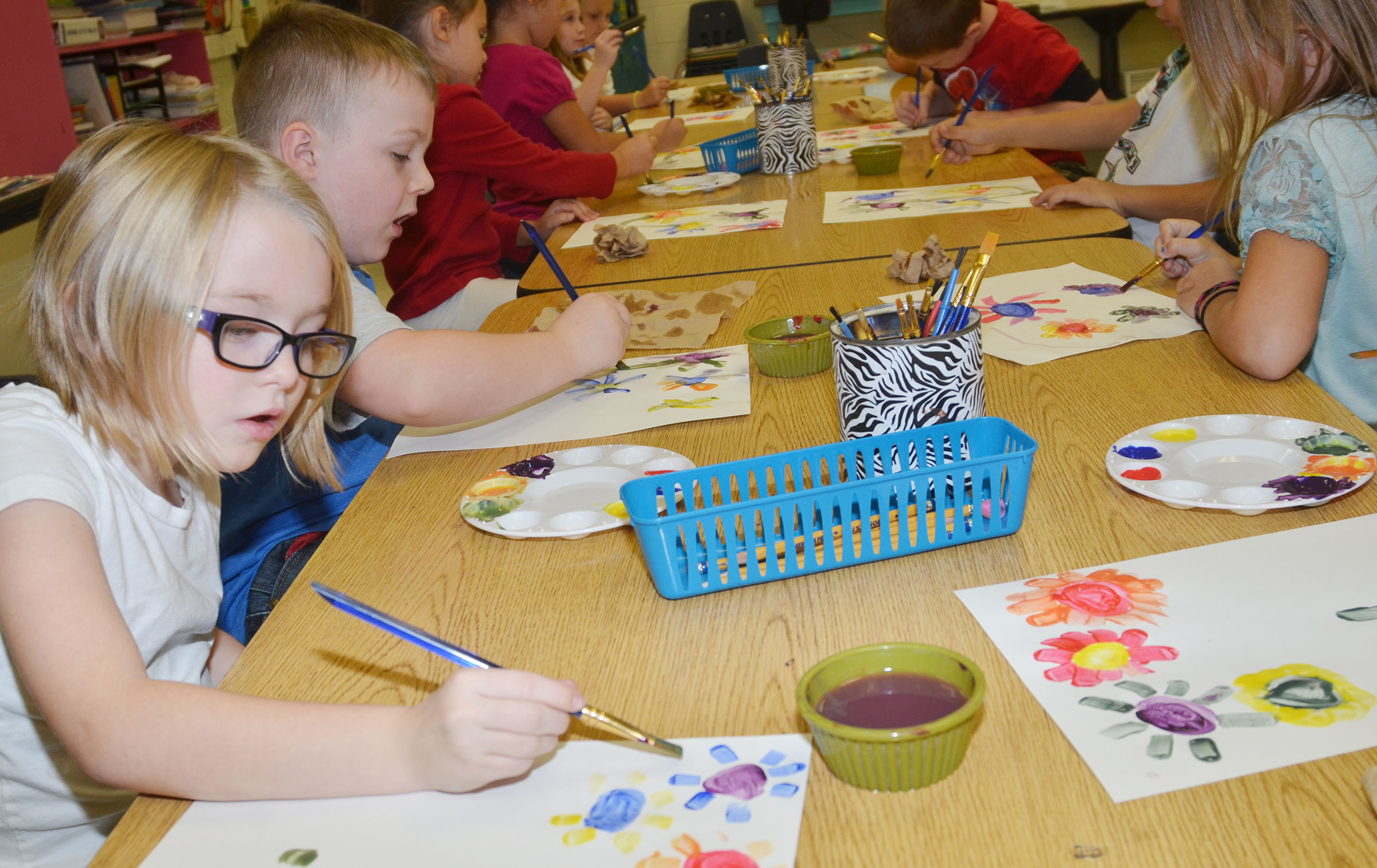 "CES first-grader Madelyn Brunelle and her classmates paint flowers to replicate Picasso's artwork ""Hands with Flowers."""