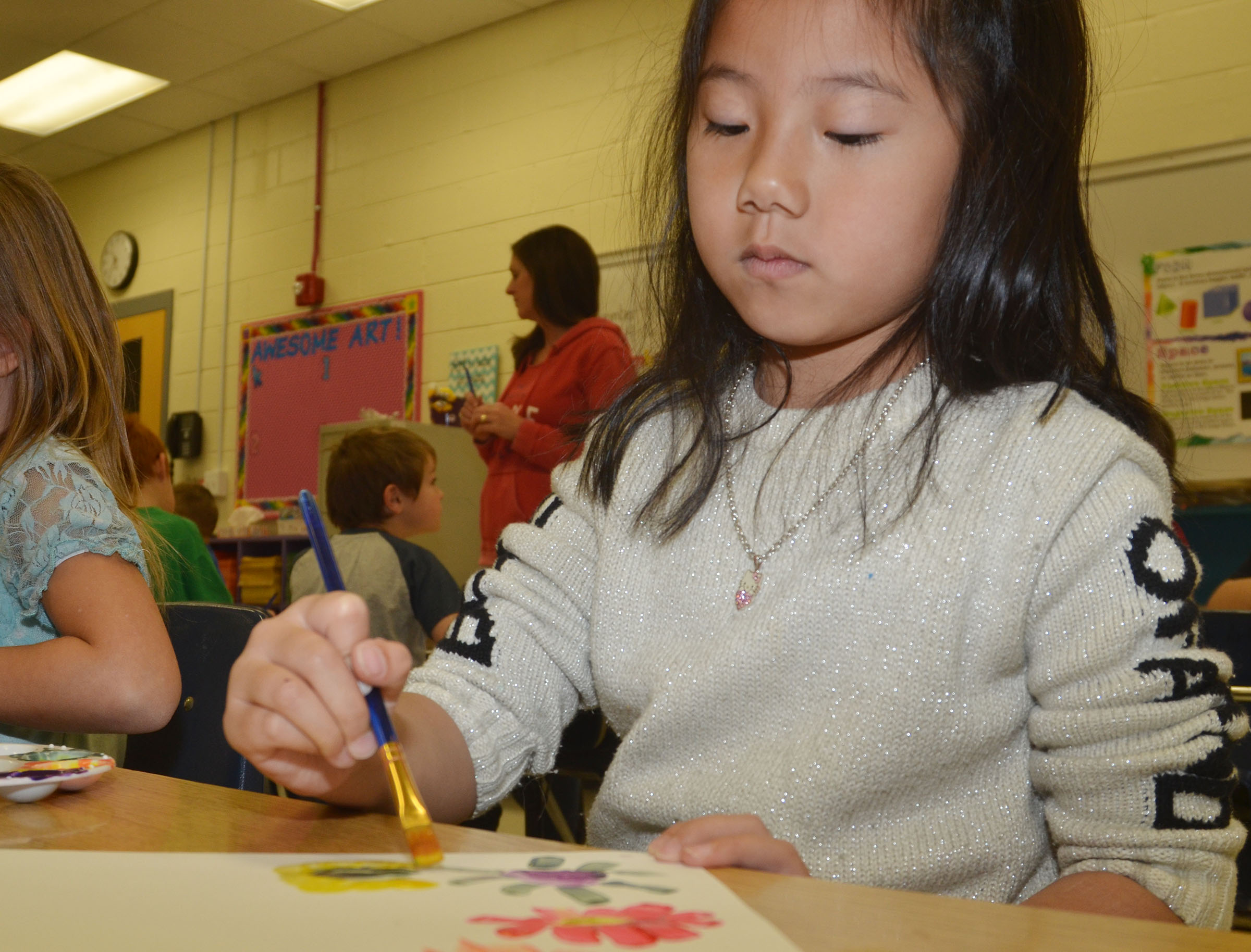 "CES first-grader Tina Jiang paints flowers to replicate Picasso's artwork ""Hands with Flowers."""