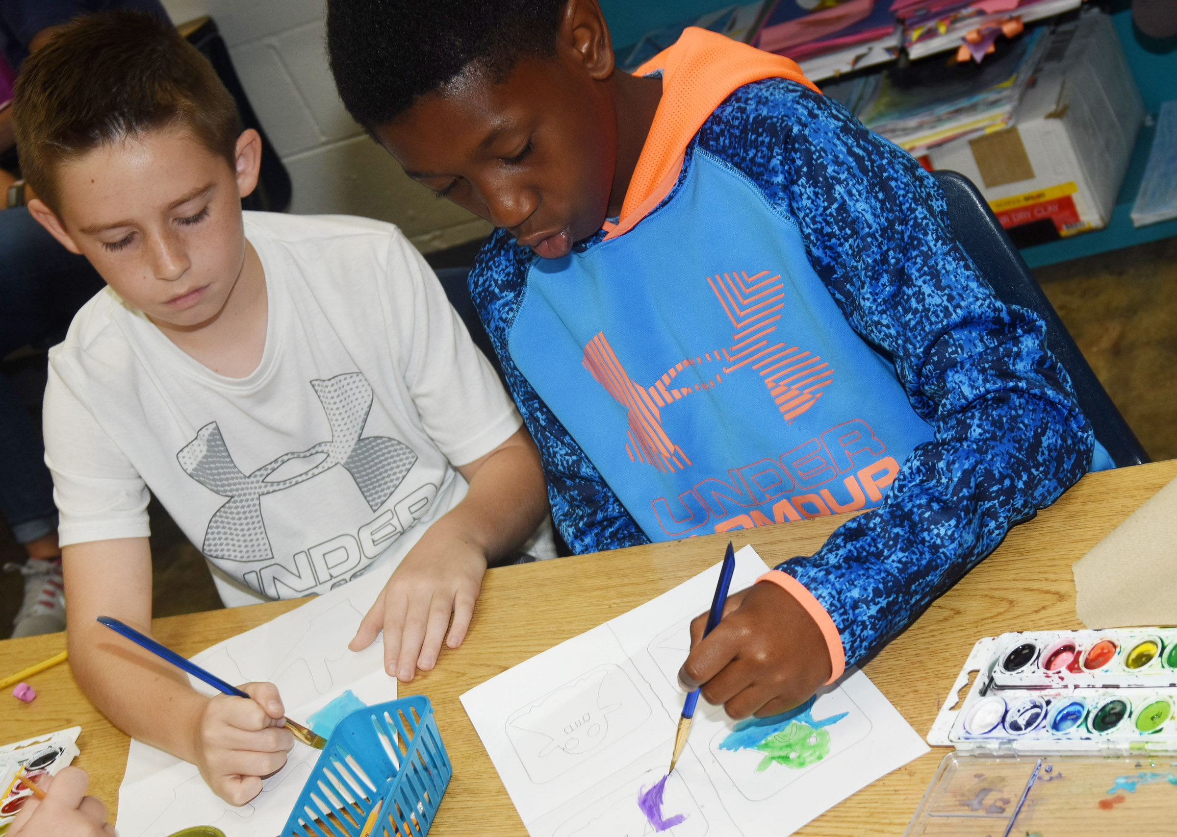 CES fourth-graders Luke Adkins, at left, and Jaron Johnson paint their pop art.