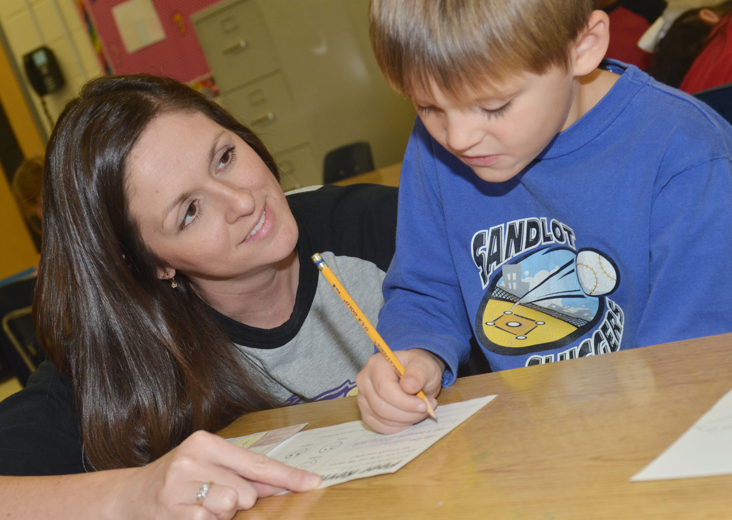 CES art teacher Adrienne Hash helps first-grader Seeley Whitaker write his art review.