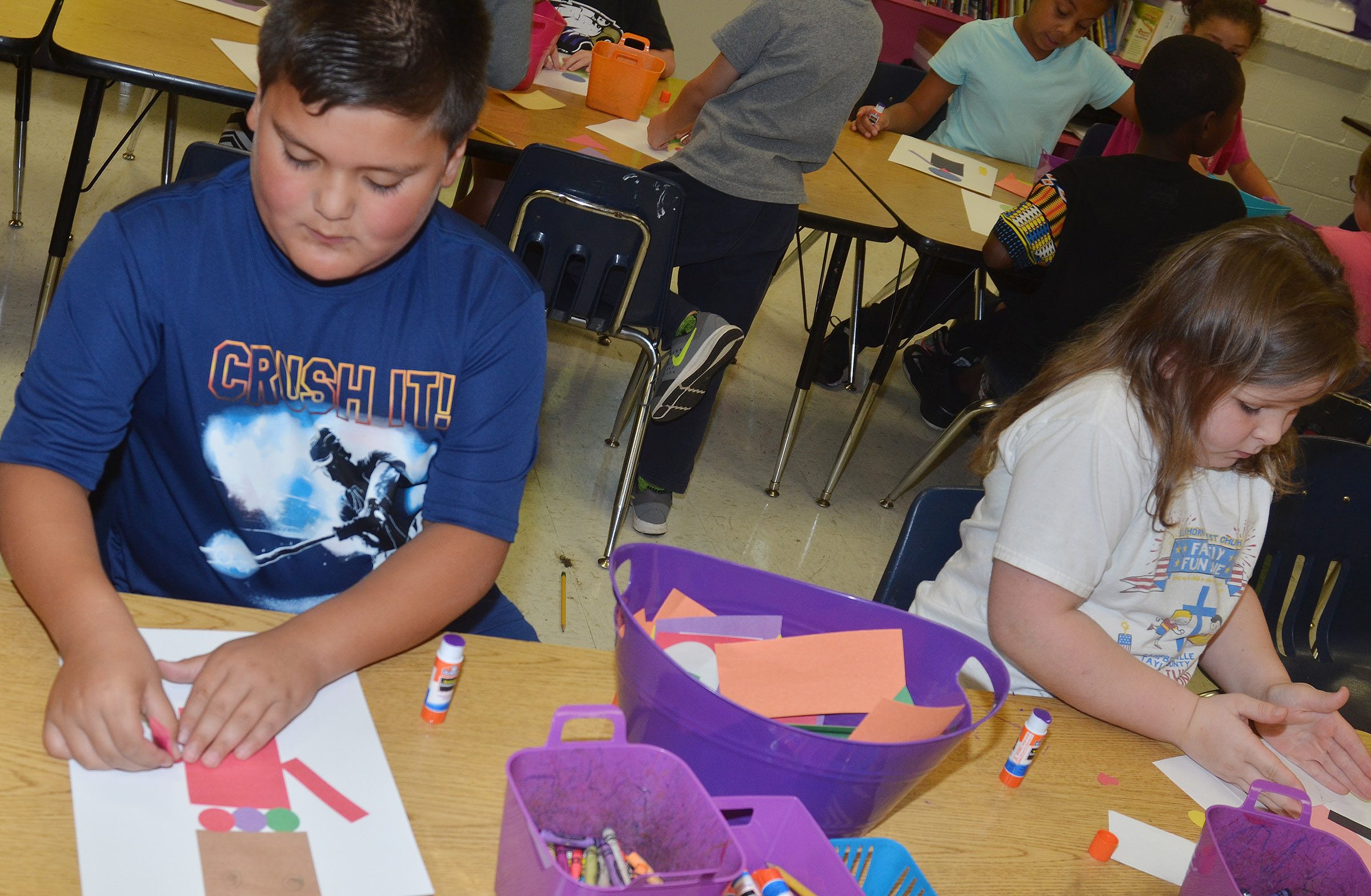 CES second-grader Eric Mixtega, at left, and Kierra Maupin glue their robots together.