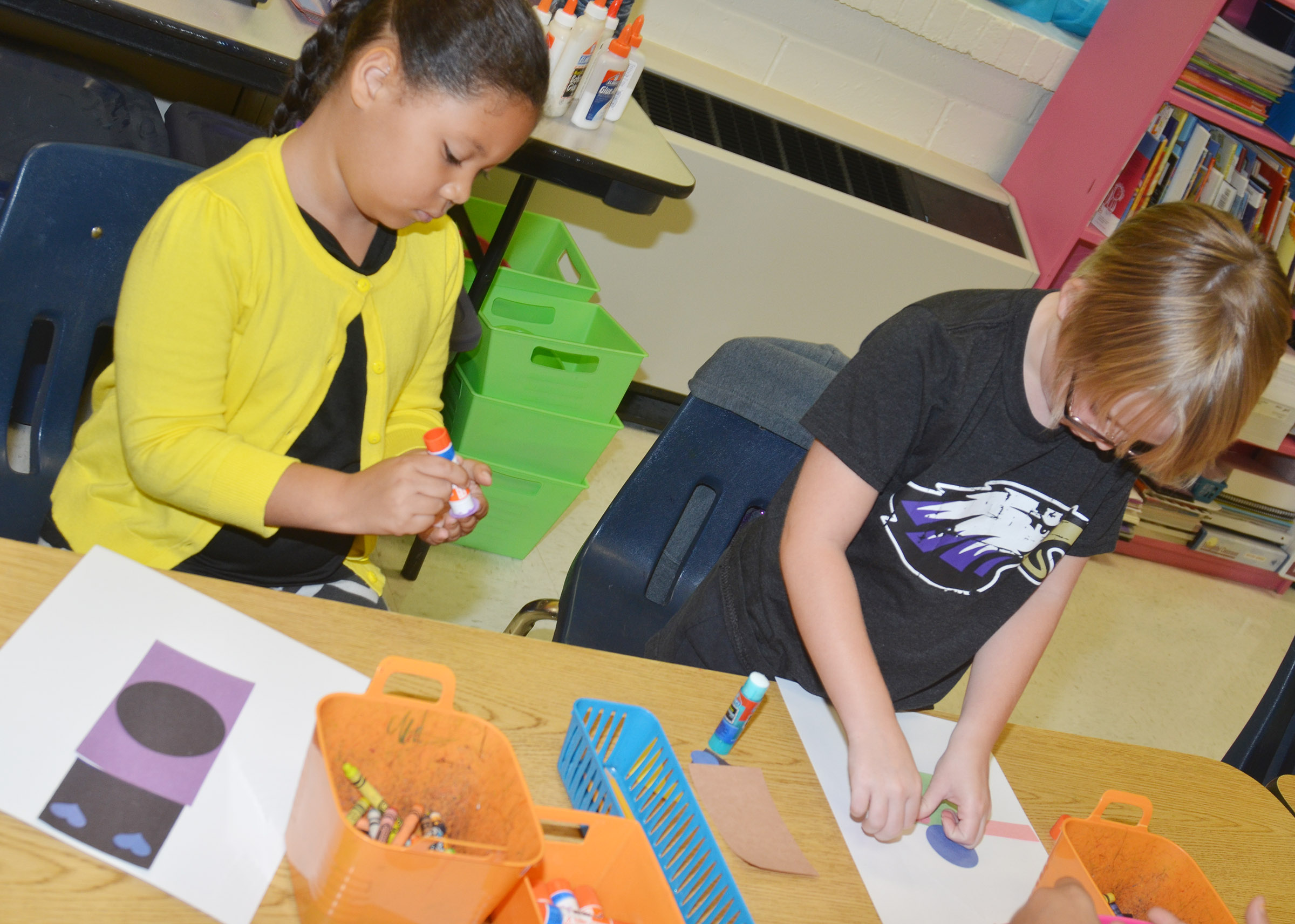 CES second-graders Briana Wooley, at left, and Maddie Brunelle glue together their robots.