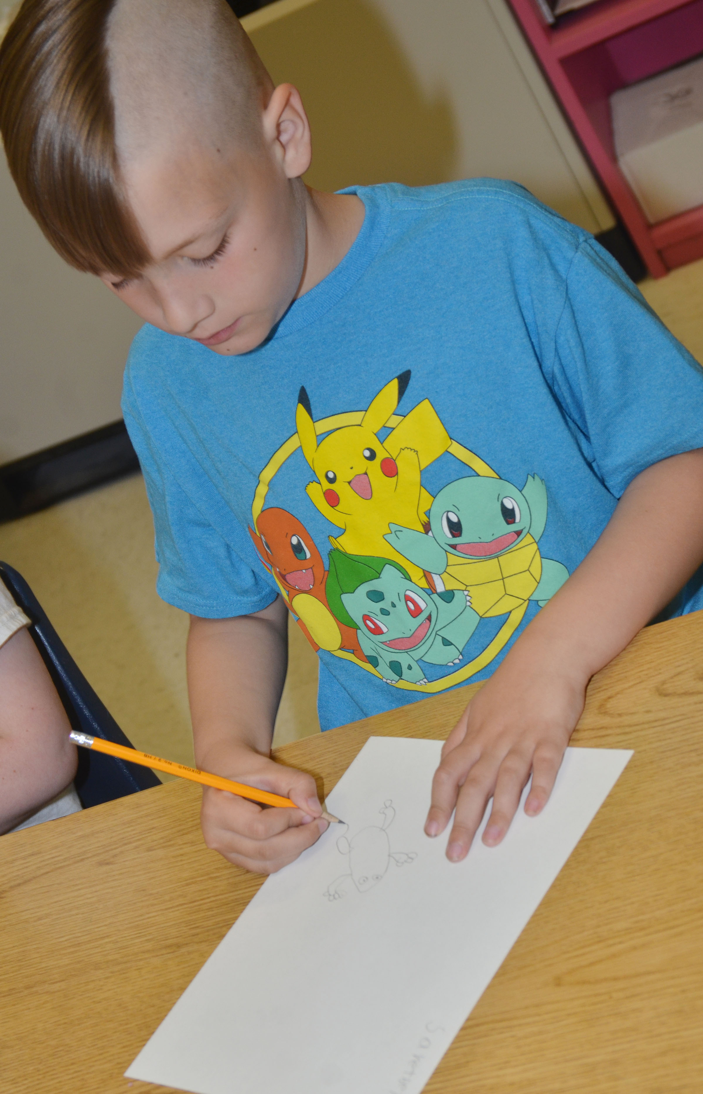 CES third-grader Izak Burress draws his frog scene for the Save the Frogs contest.