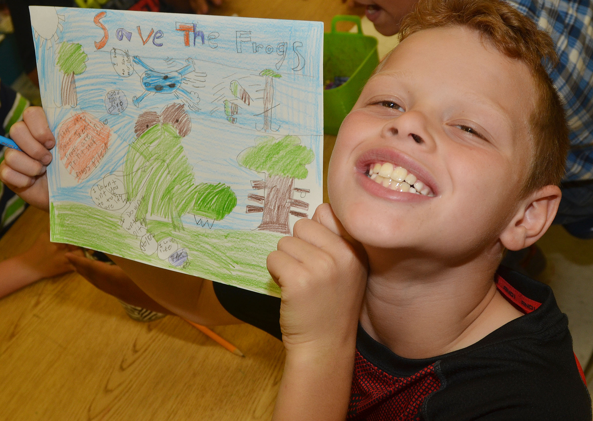 CES third-grader Demetrious Dickens holds his completed Save the Frogs contest artwork.