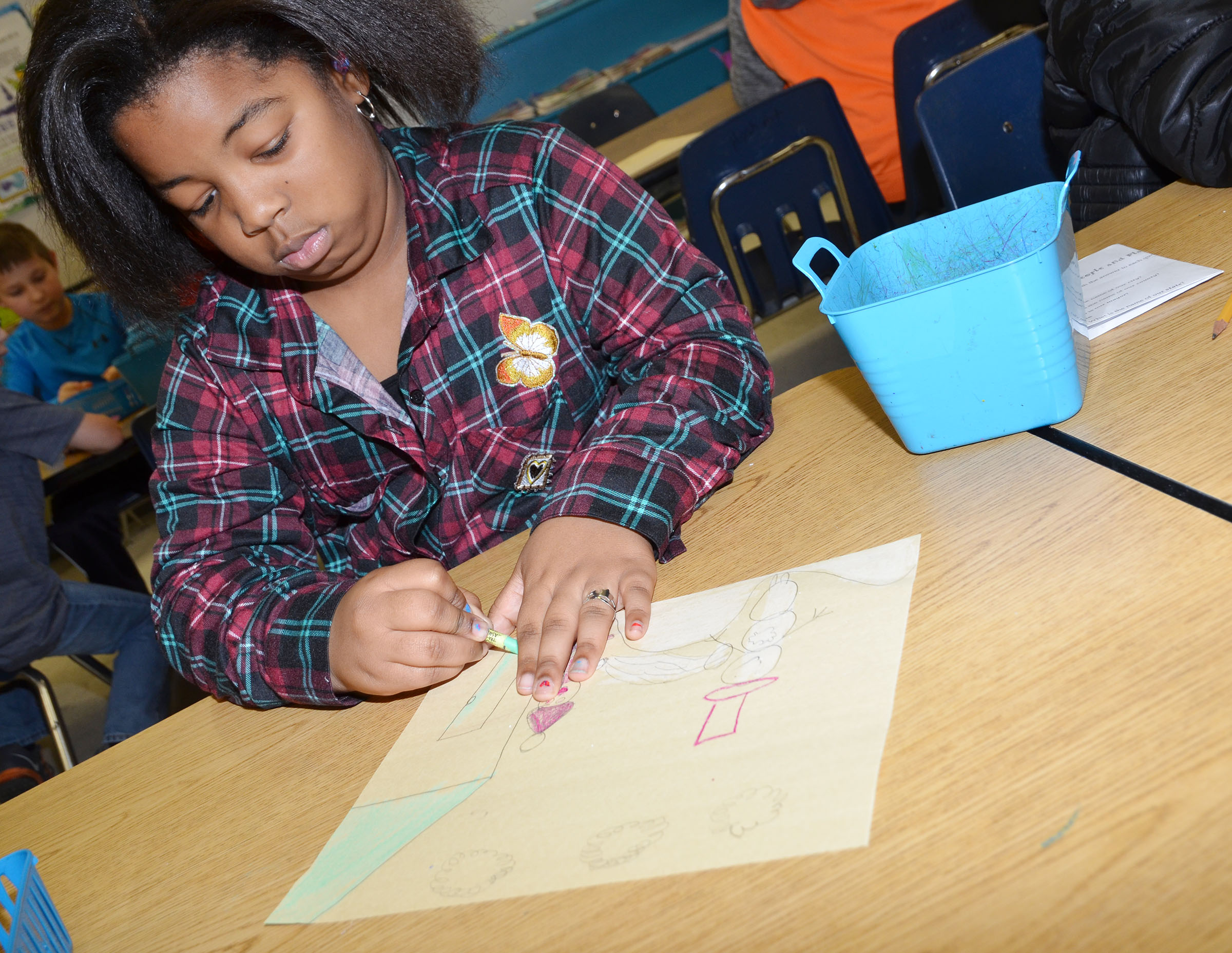 CES third-grader KaMiya Williams colors her snow picture.