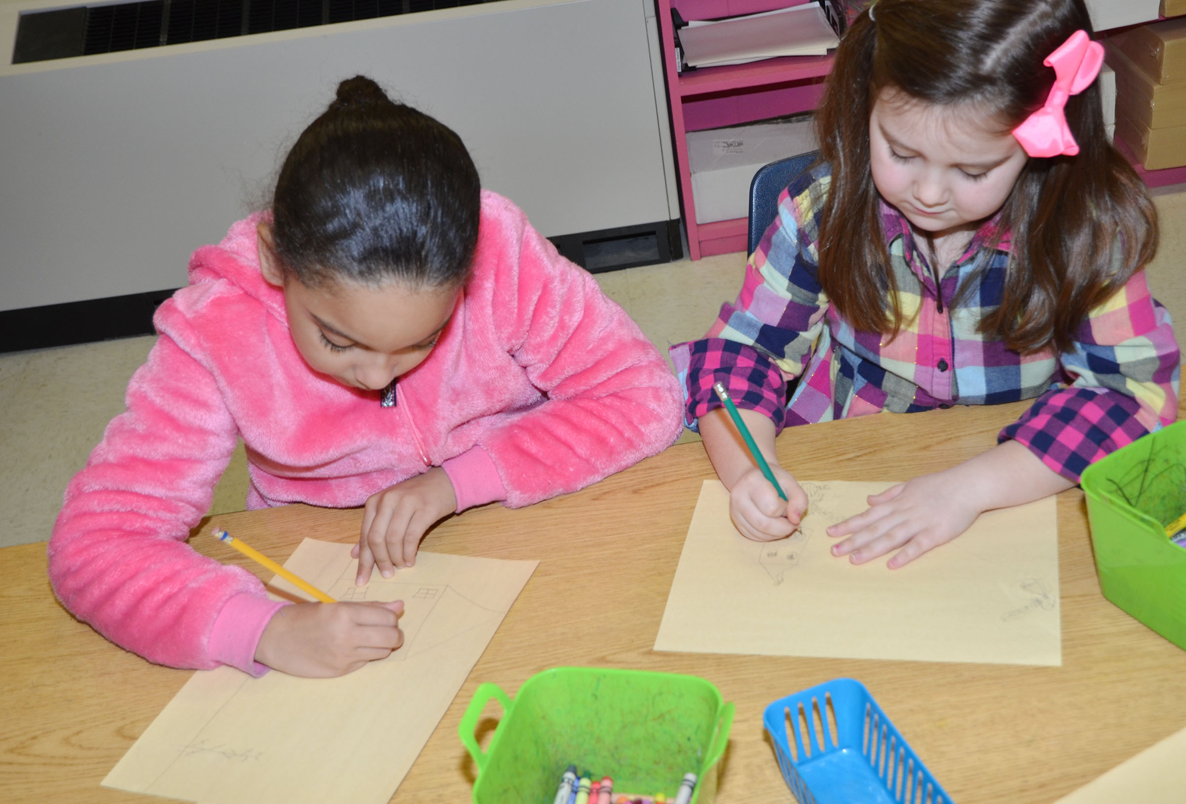 CES third-graders Aleecia Knezevic, at left, and Maylee Wilds draw their snow pictures.