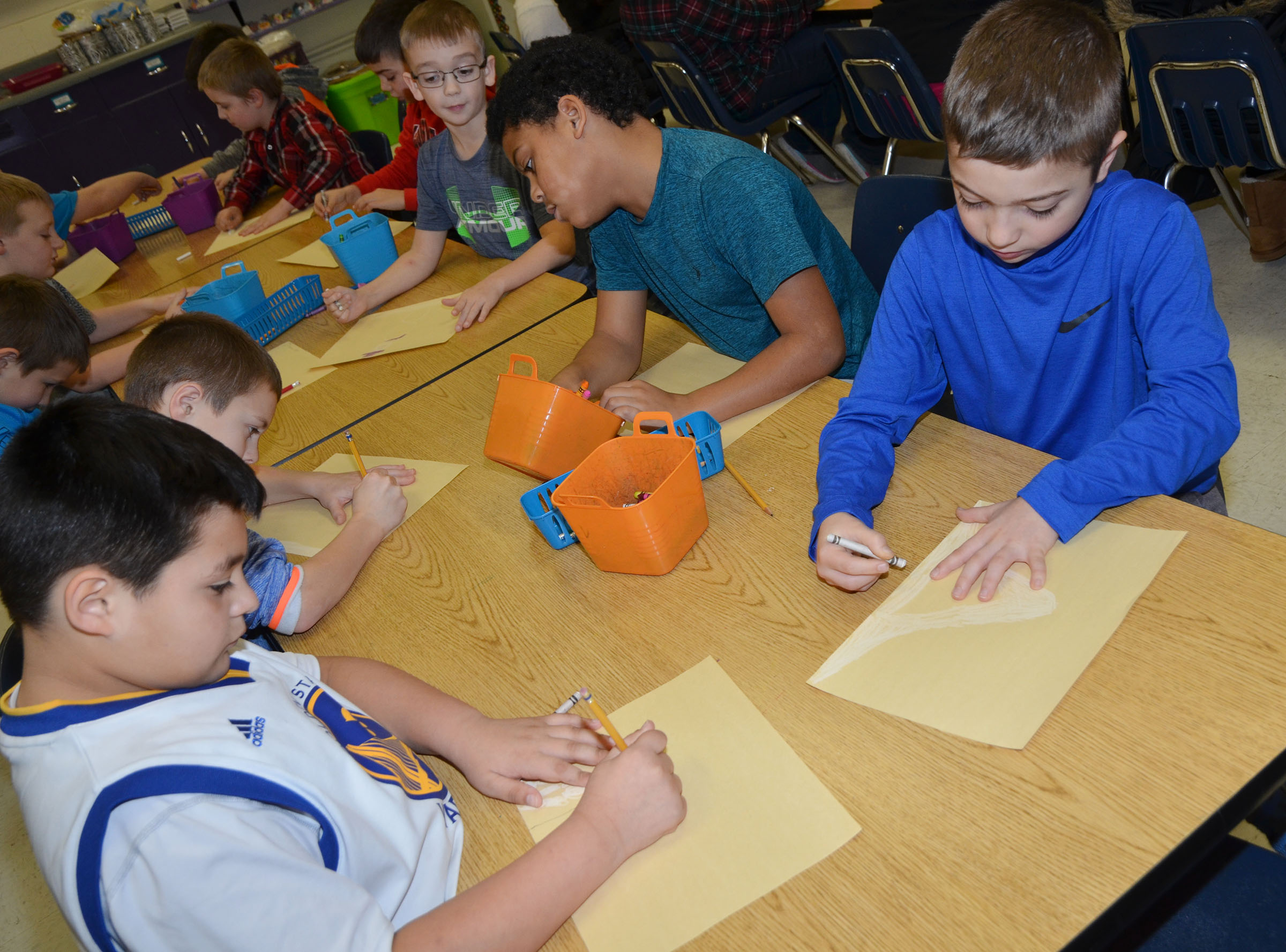 CES third-grader Braydon Paiz, at left, and Carson Mills color their snow pictures.