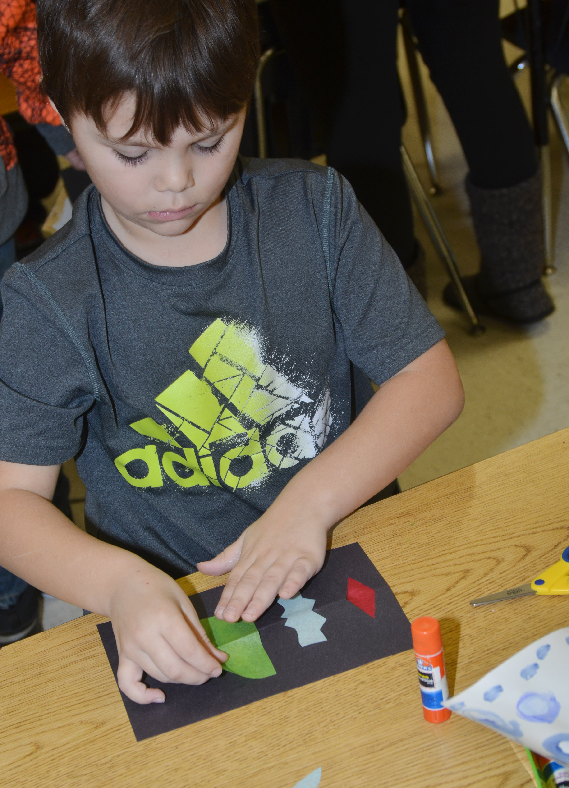 CES first-grader Jaxson Hunt glues tissue paper on his stained glass window.