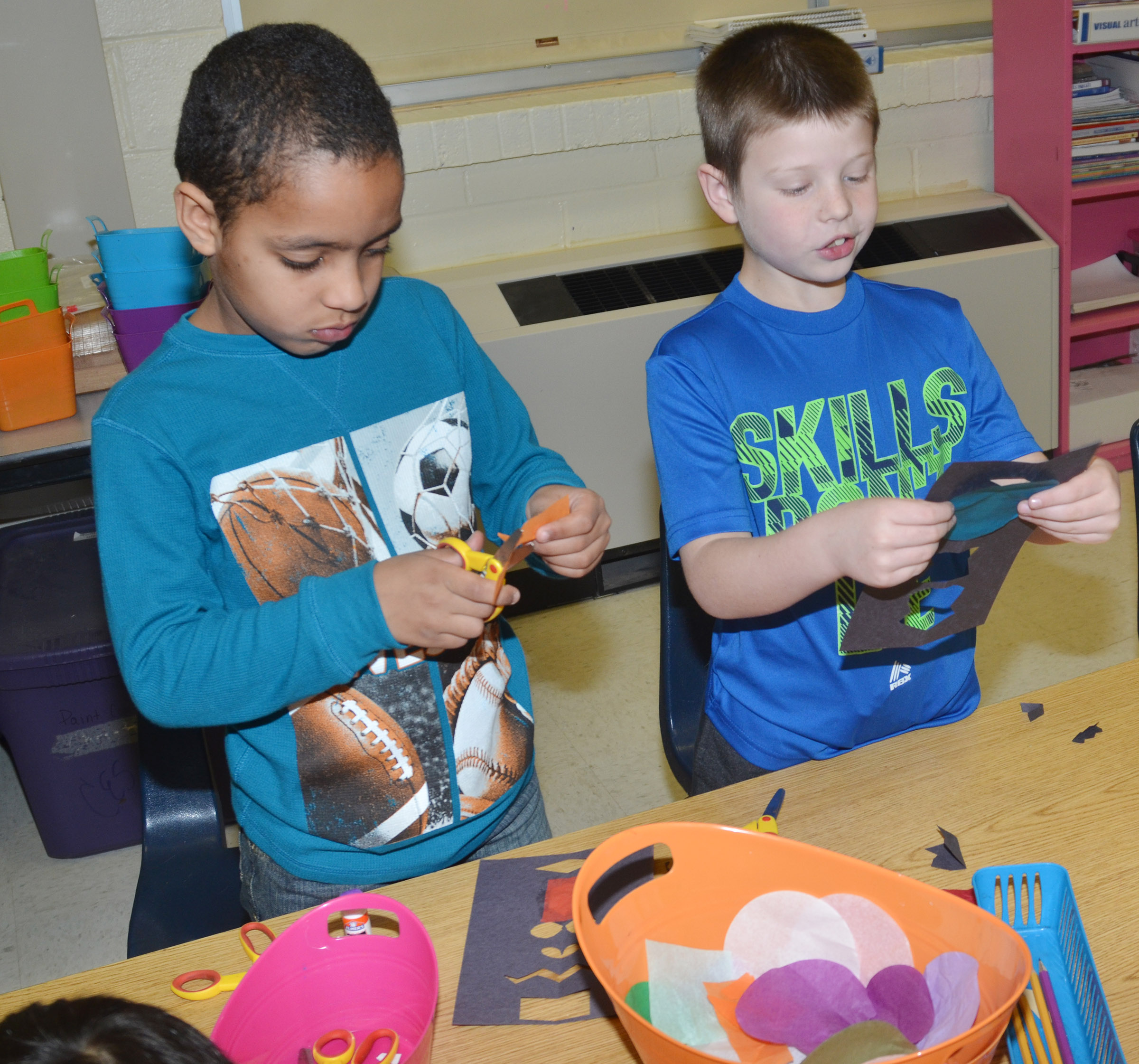 CES first-graders Jo'van Goins, at left, and Brody Sidebottom glue their stained glass windows.