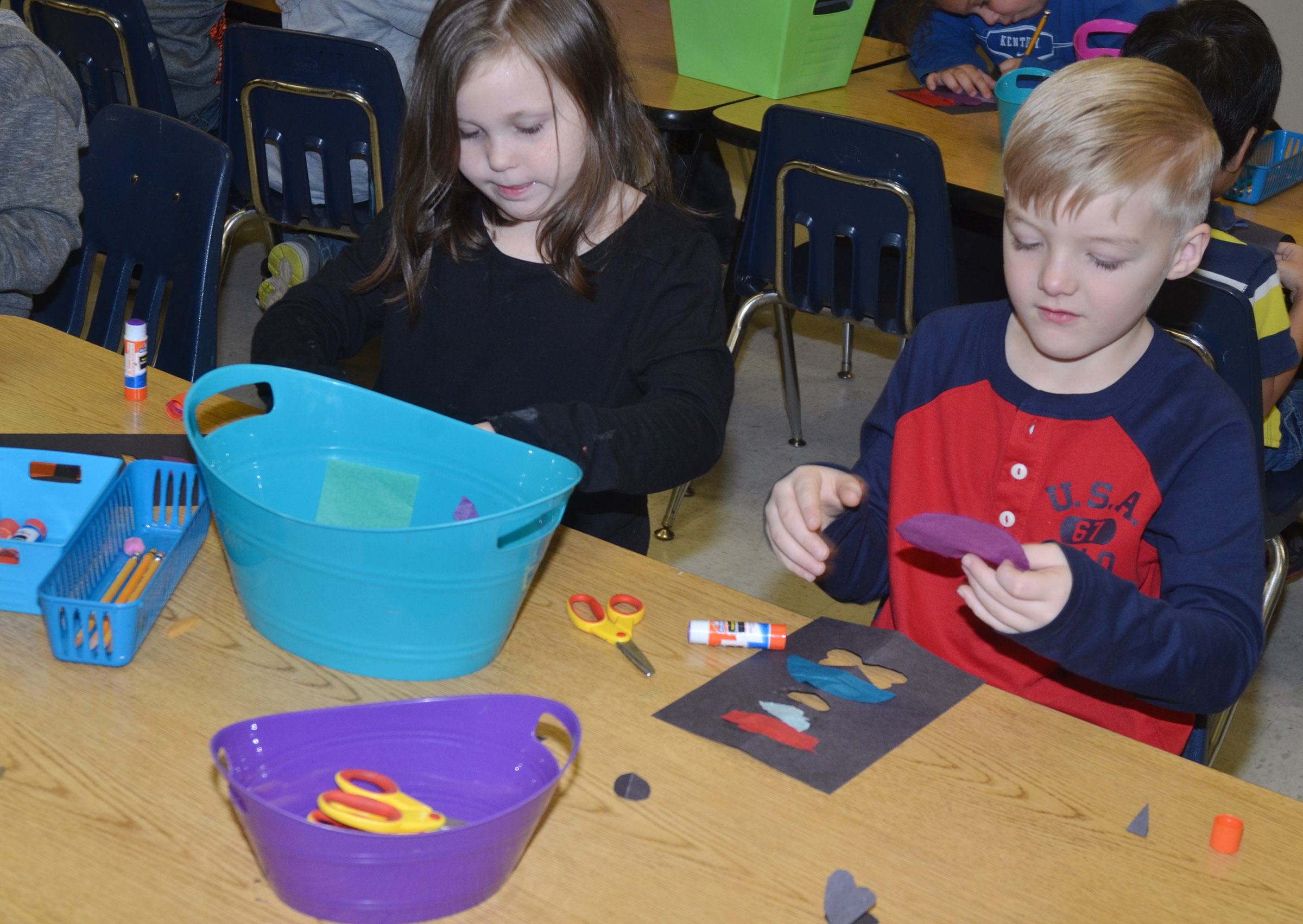 CES first-graders Cadynce Cox, at left, and Samuel Scharbrough glue their stained glass windows.