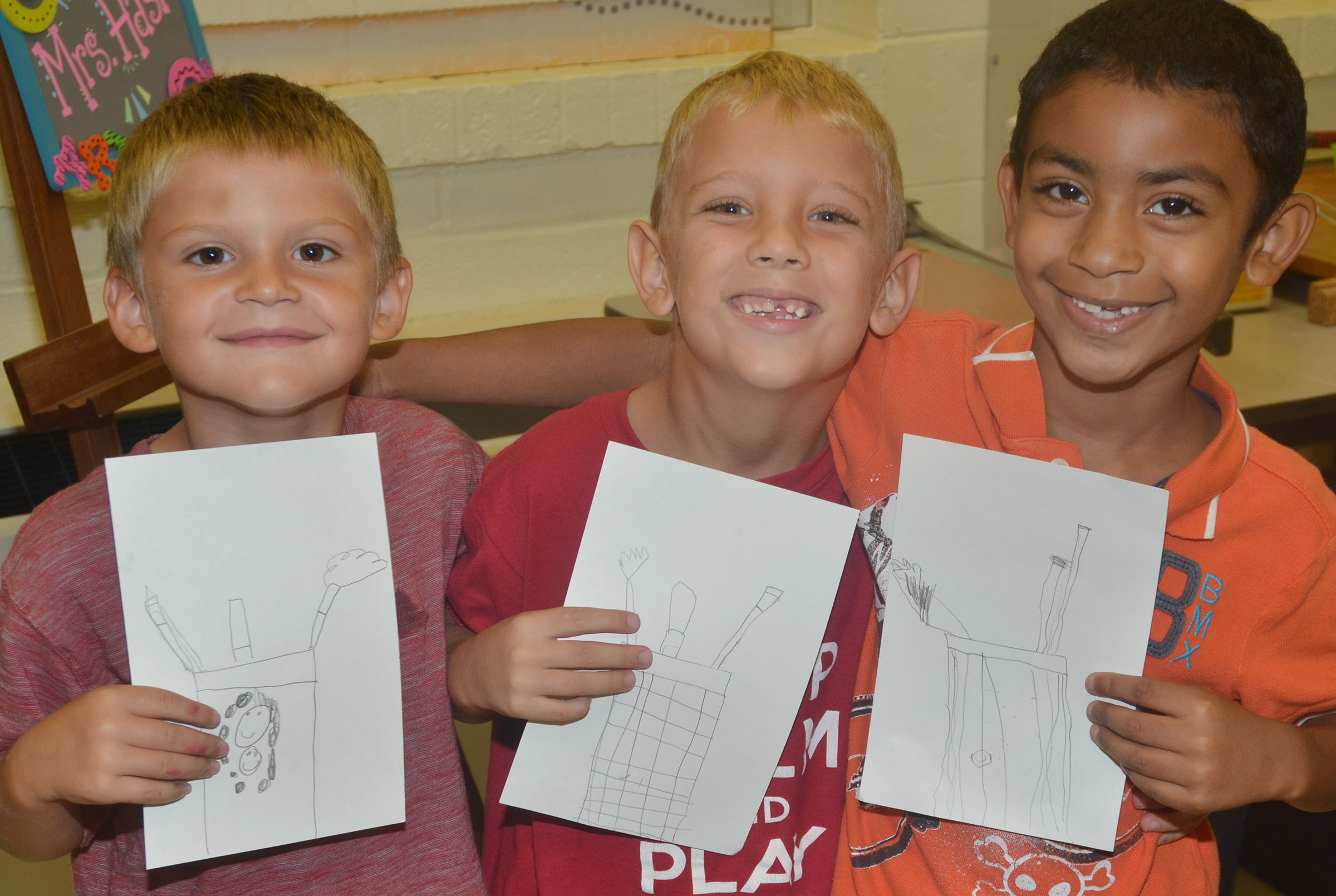 CES first-graders, from left, Seeley Whitaker, Gabe Prior and Enoch Smith hold their finished still life drawings.